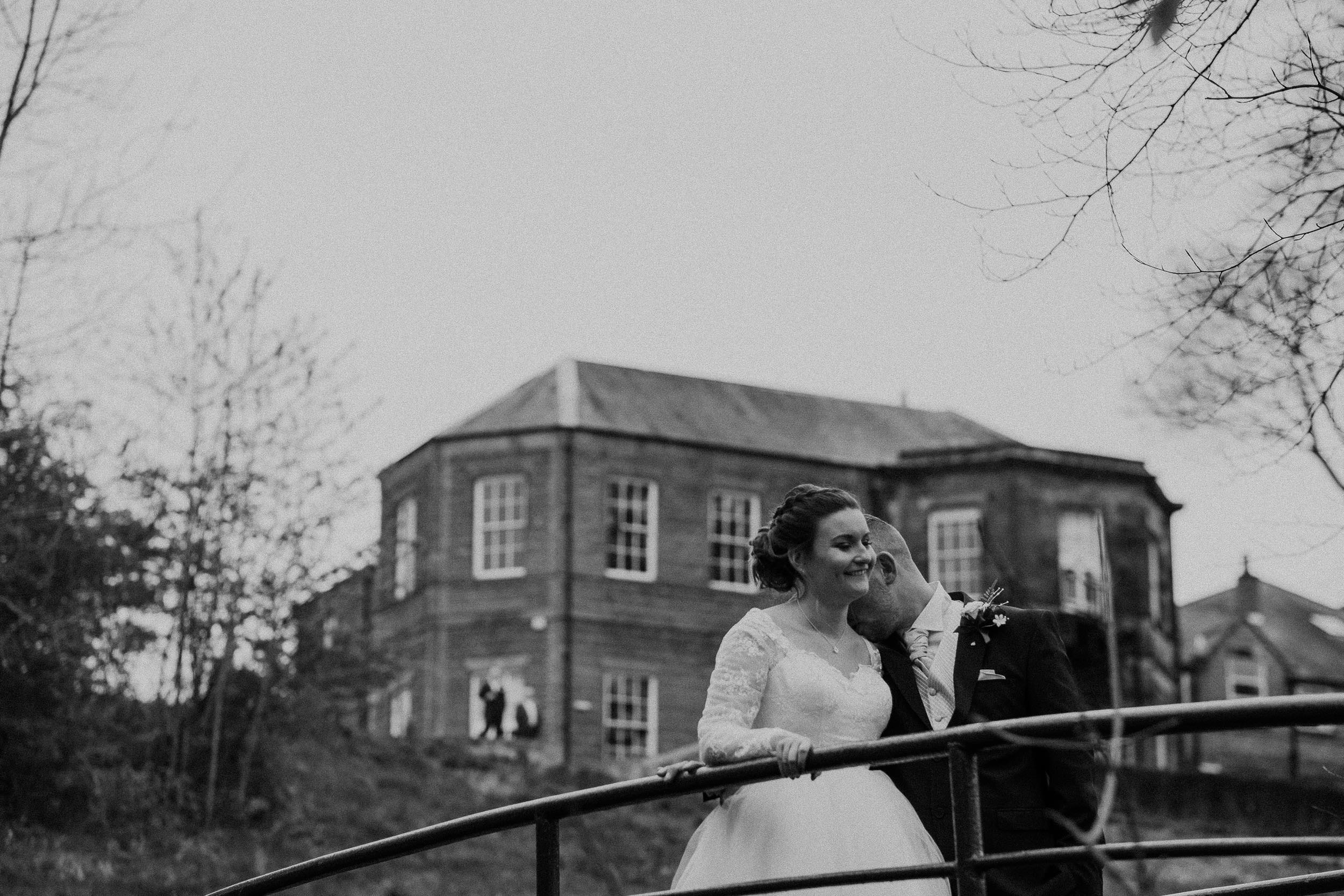 Black and white photo of groom kissing brides neck with Wallsend Hall behind