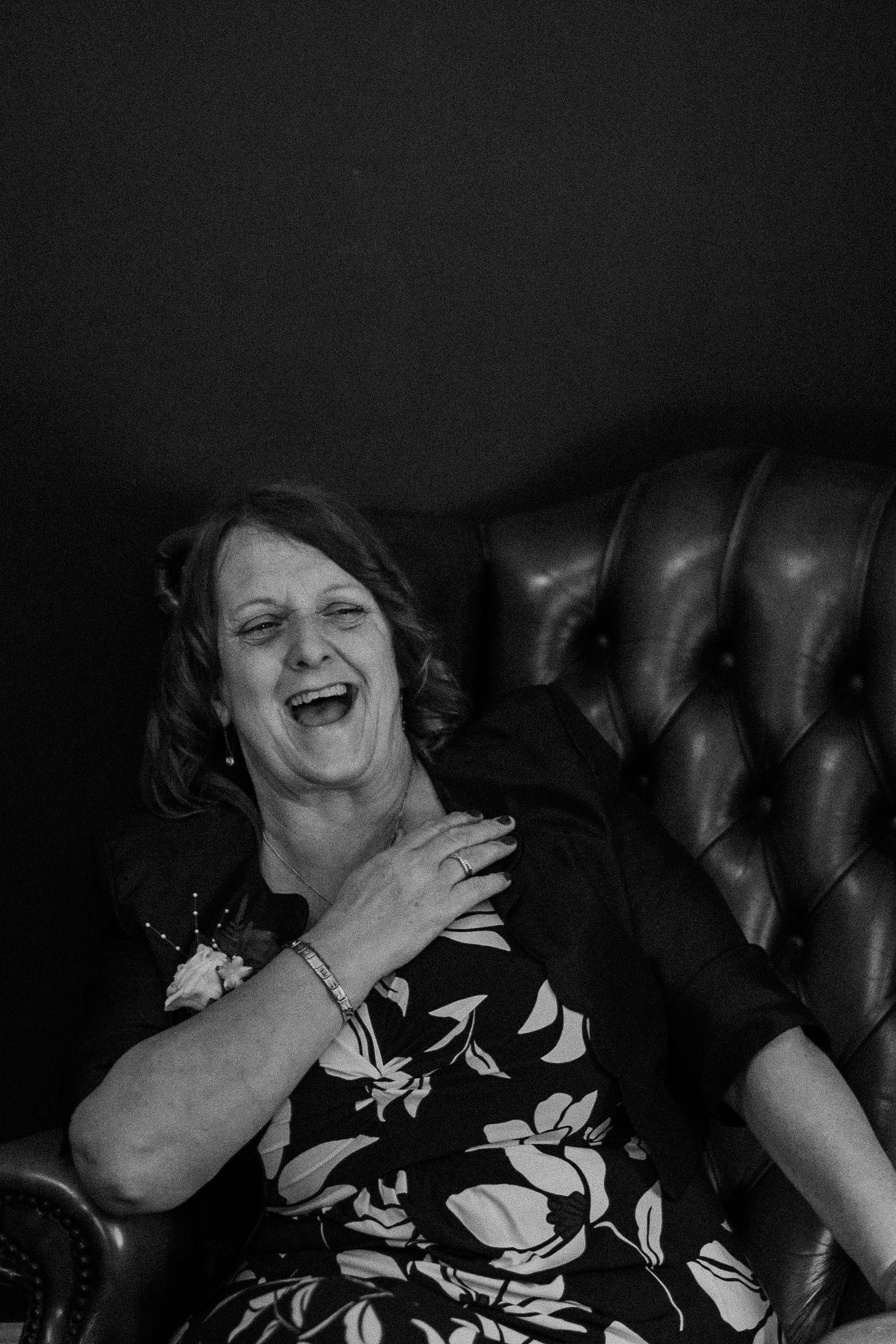 Black and white photo of wedding guest laughing