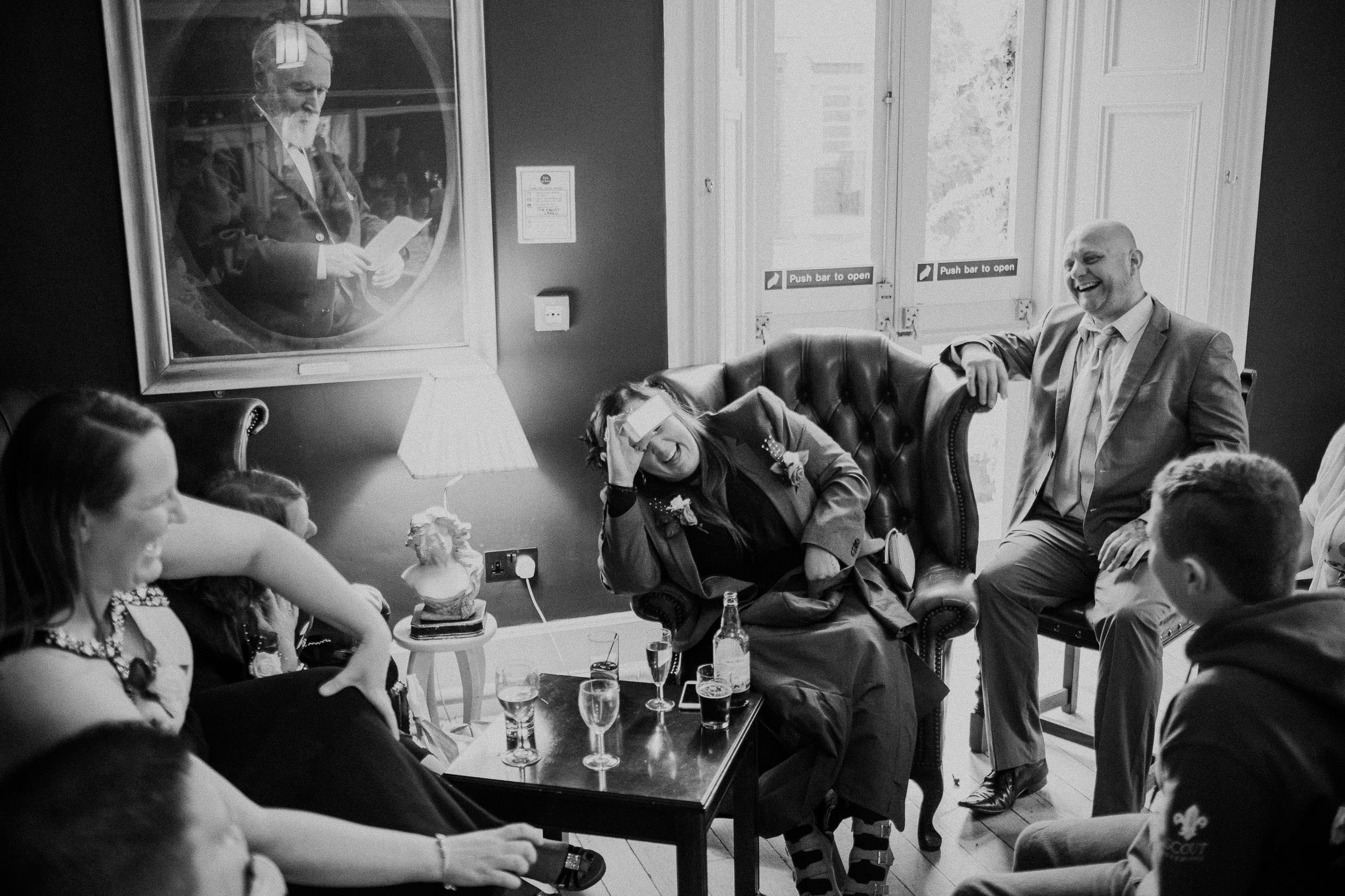 Black and white photo of wedding guests laughing while playing game