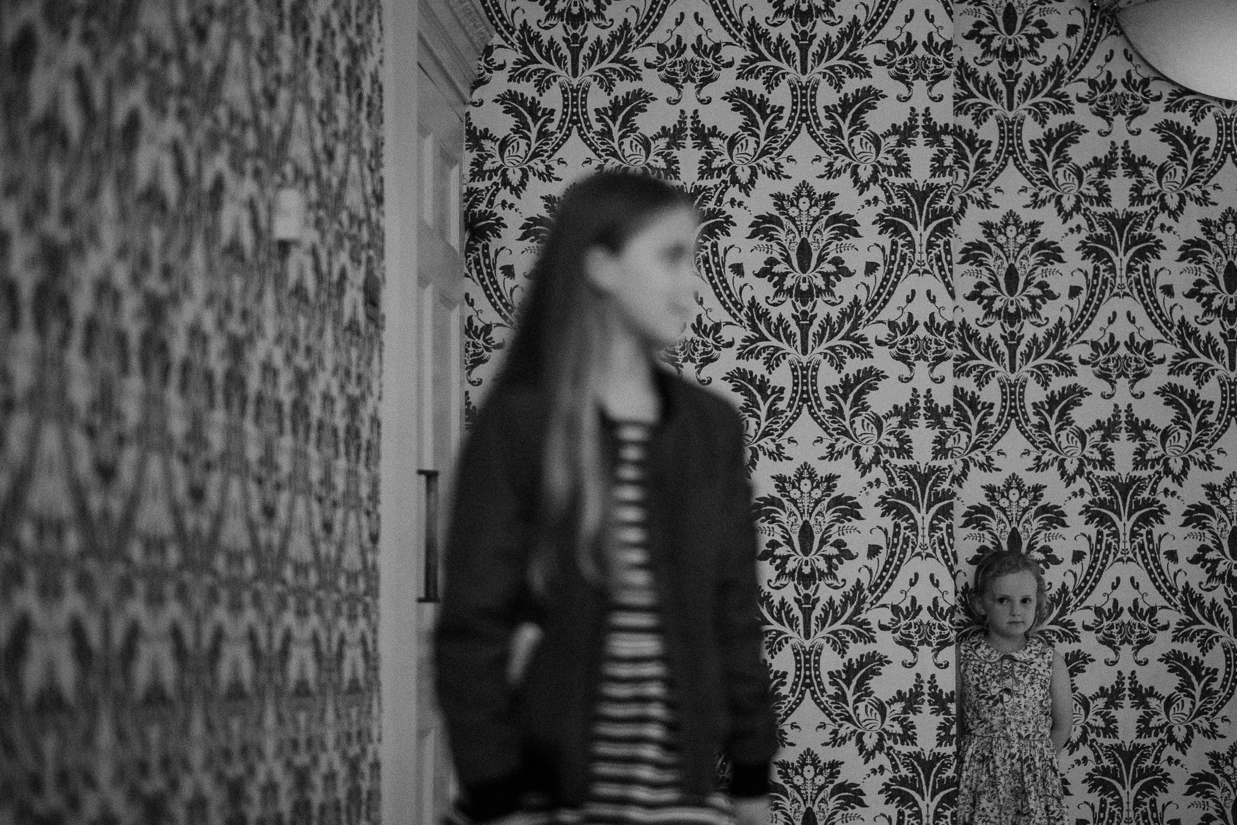 Black and white photo of girls playing hide and seek at wedding
