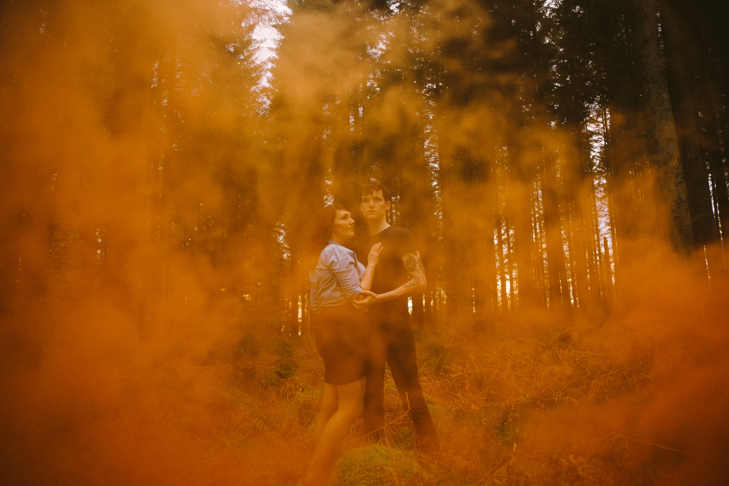 Engaged couple standing in Kielder Forest with orange smoke floating in front of them