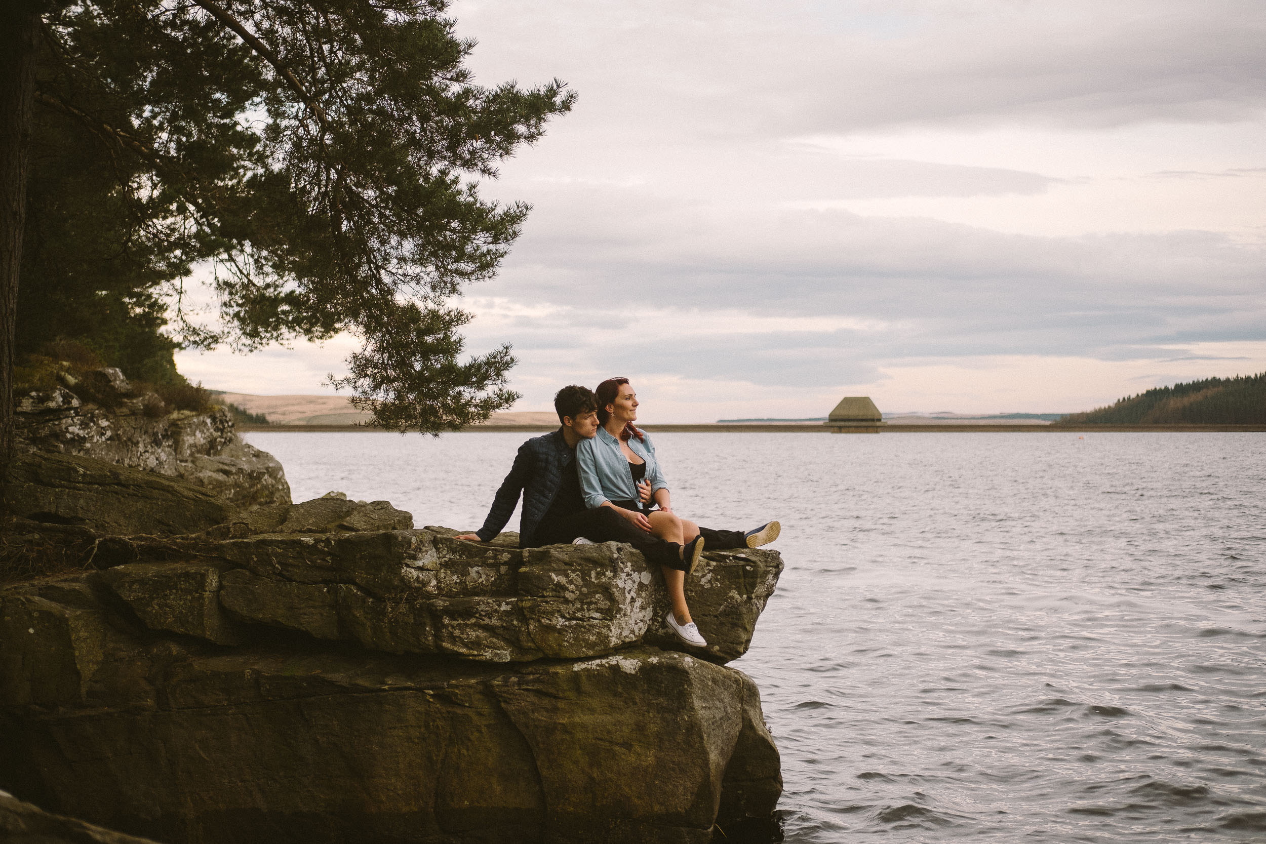Engaged couple sitting on rock looking out over Kielder Water
