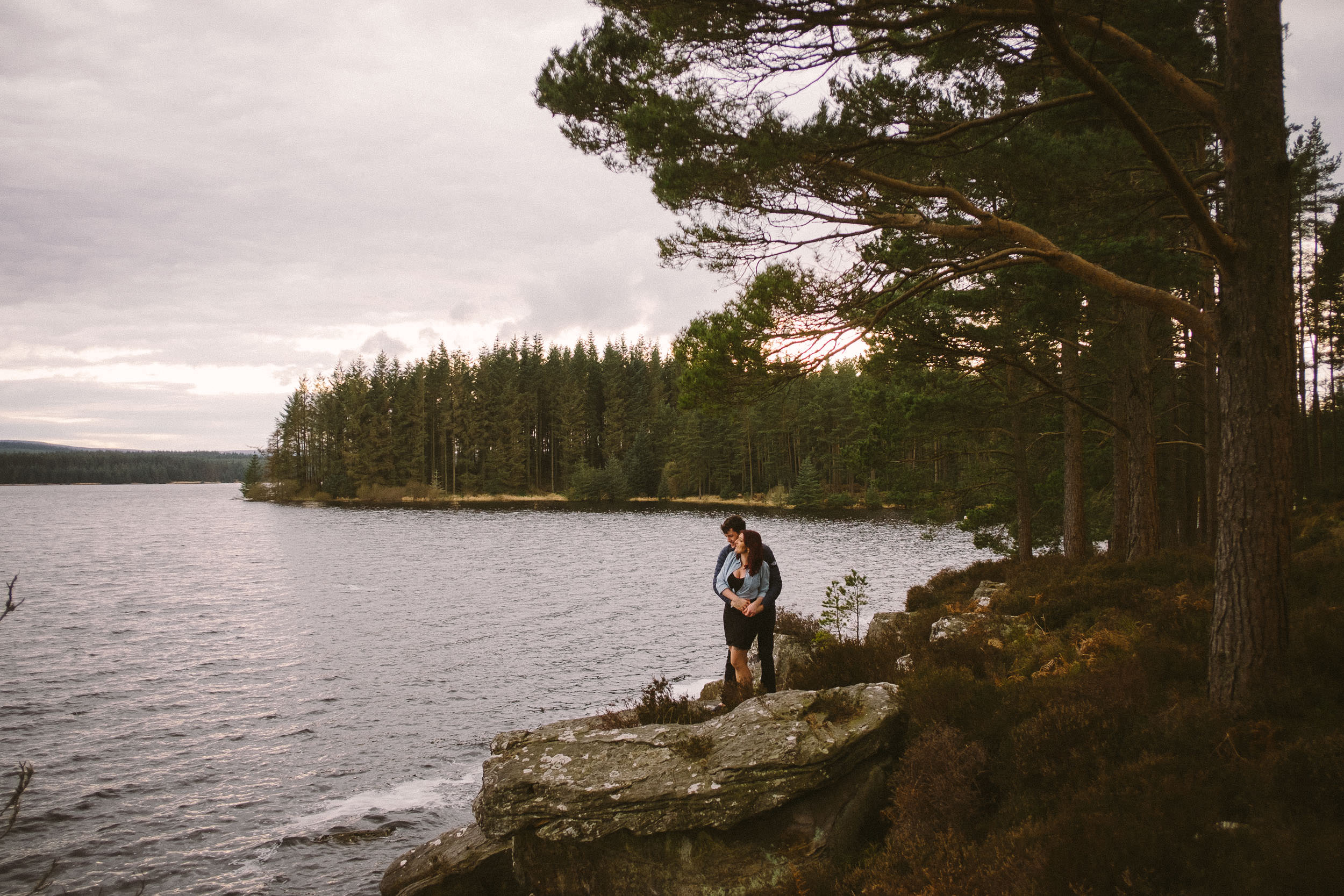 Couple cuddling on rocks looking out over Kielder Forest and Water
