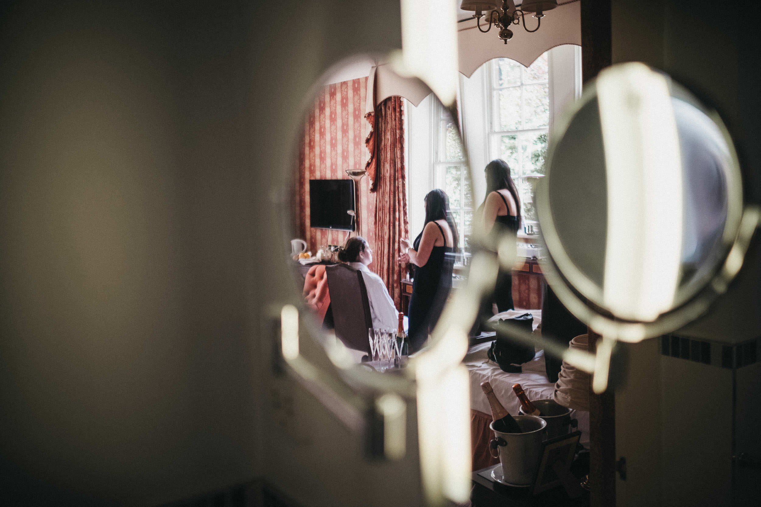 Reflections of bride getting ready in mirror