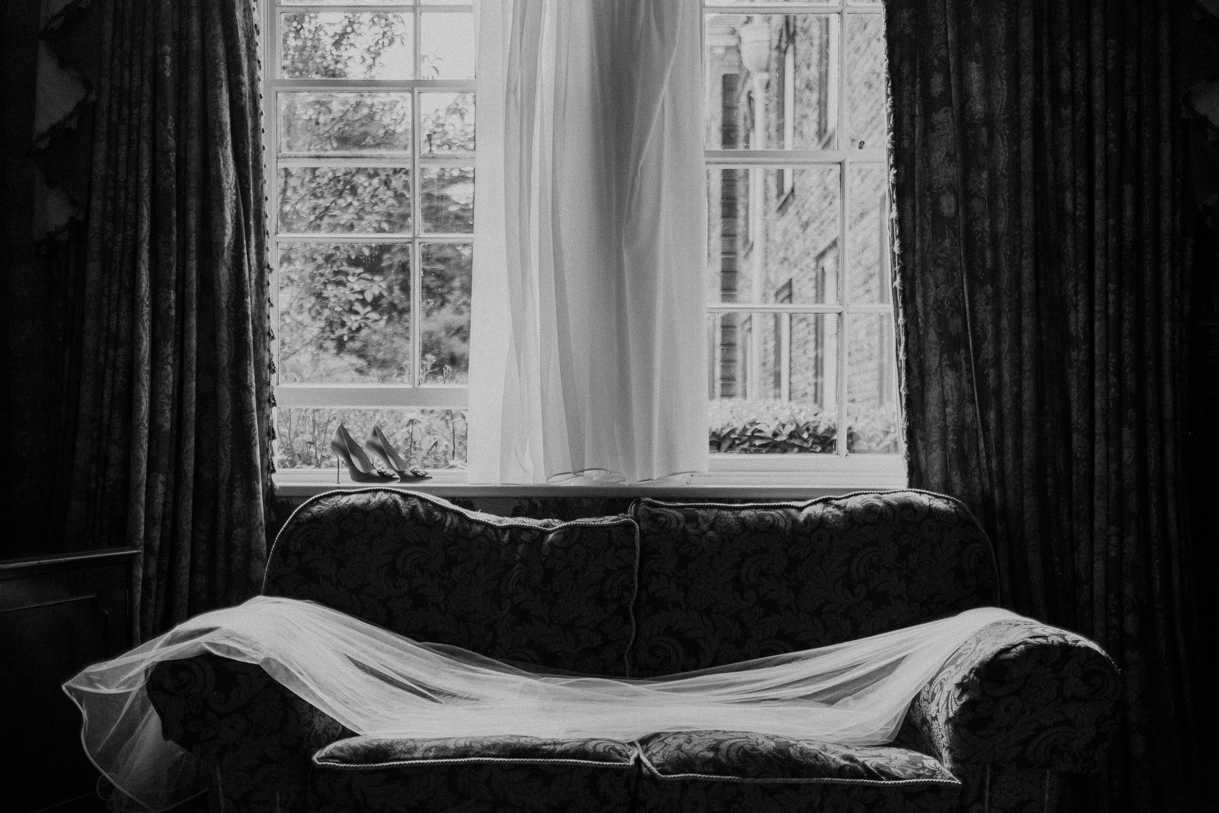 Black and white photo of dress, veil and wedding shoes
