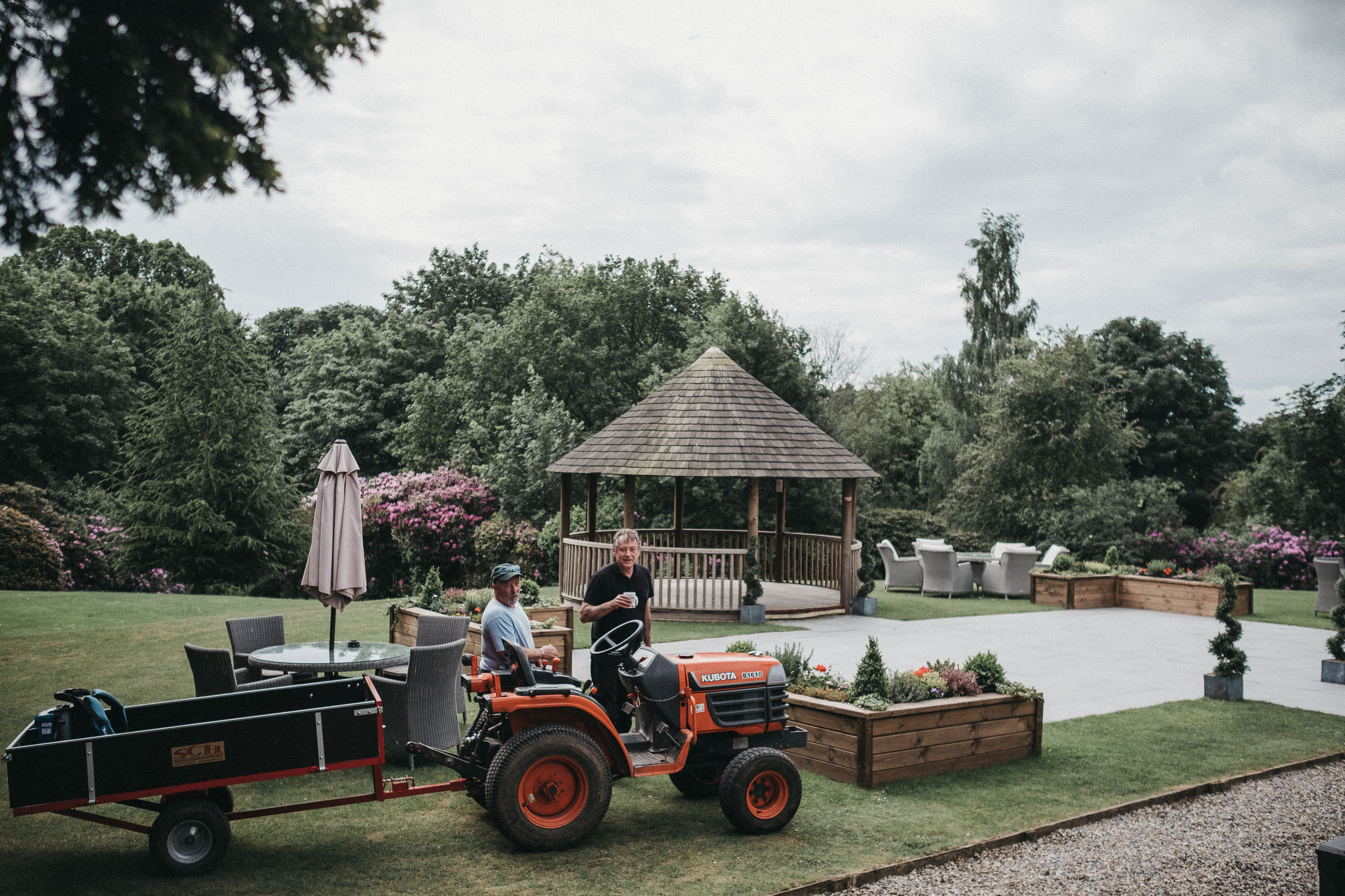 Workman having a tea break near tractor while getting gazebo ready