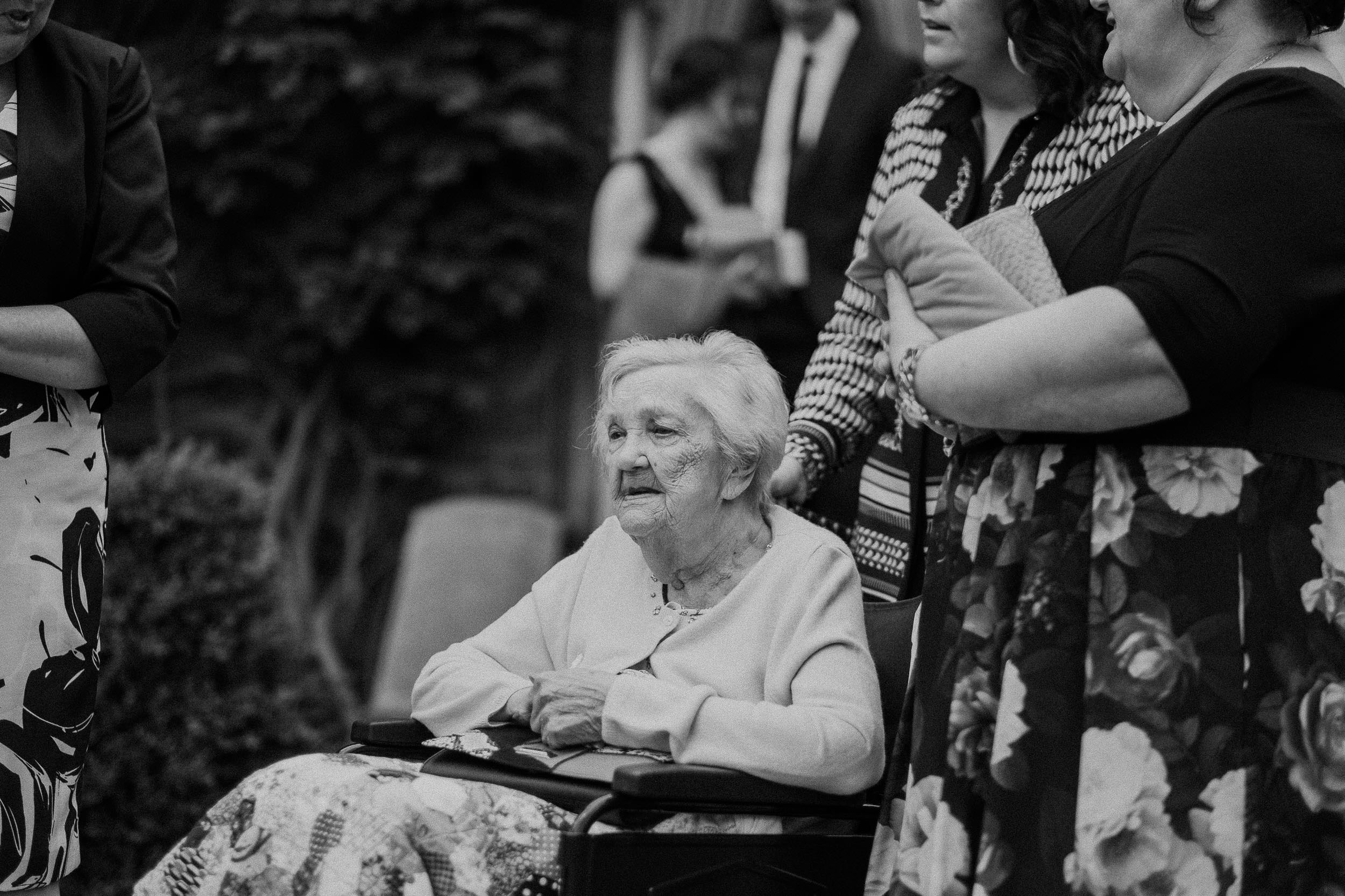 Black and white photo of older wedding guest in wheelchair