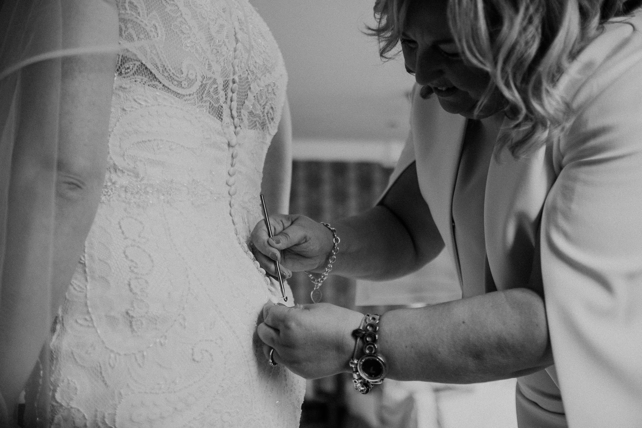 Black and white photo of mother of the bride fastening bride's dress