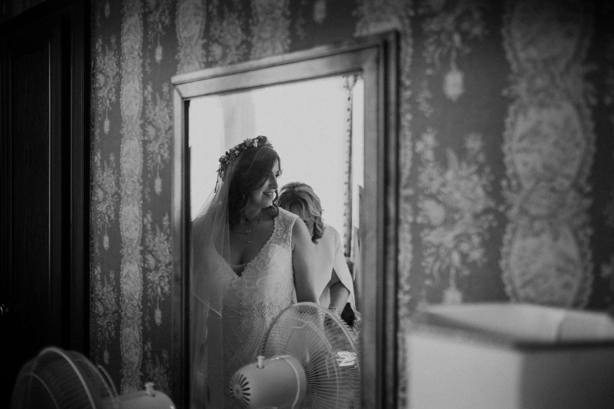 Black and white photo of bride reflected in mirror