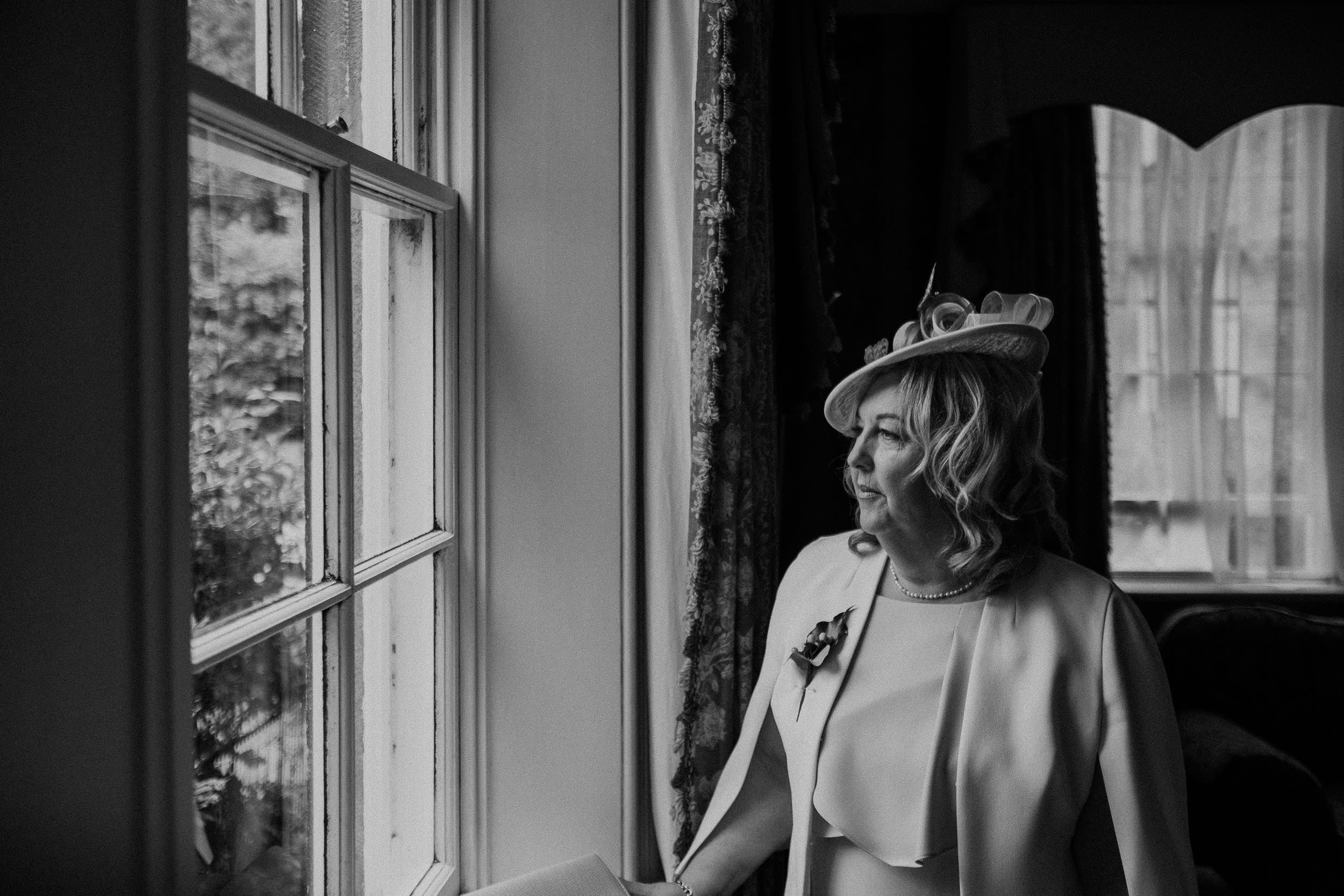 Black and white photo of mother of the bride looking out of window