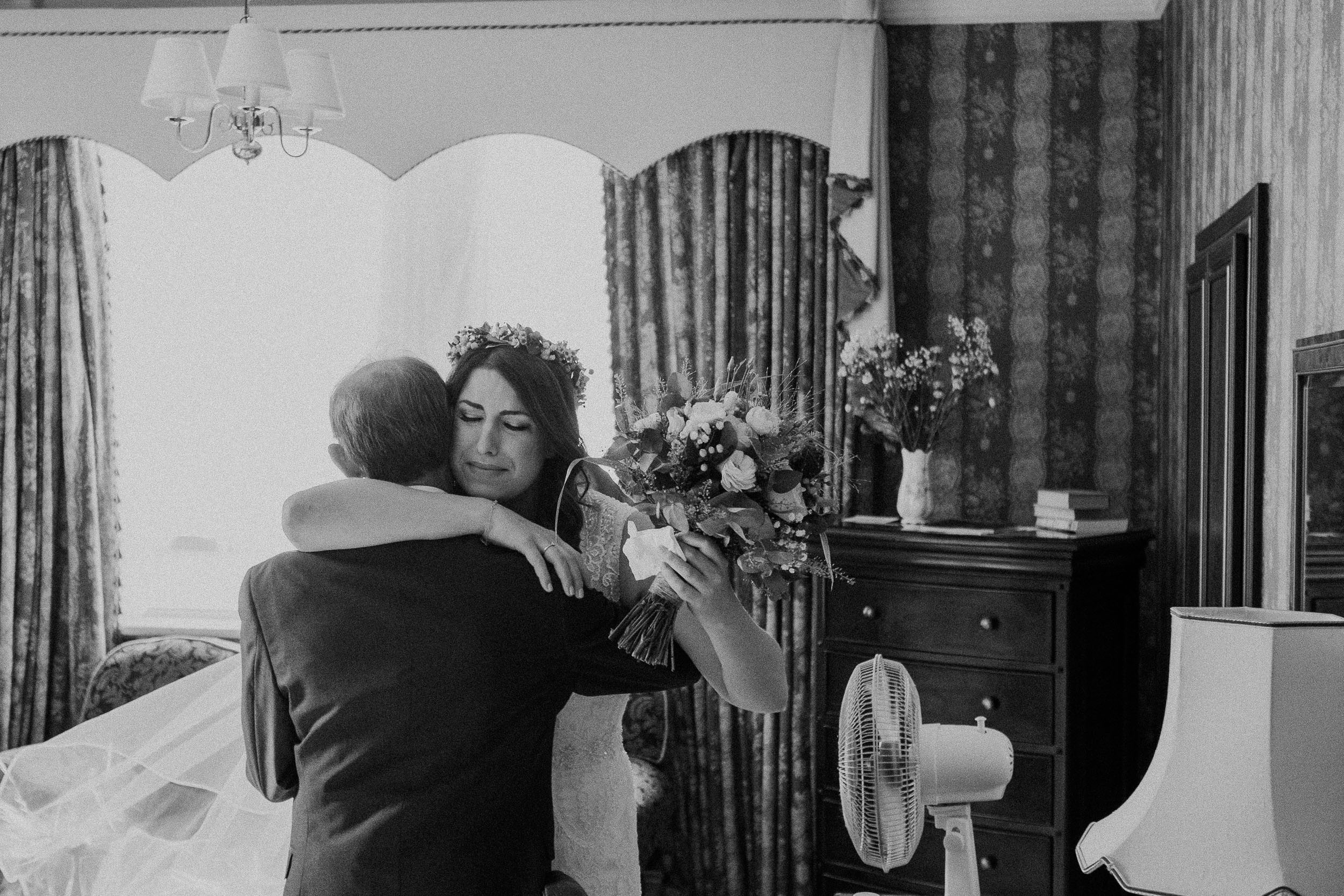 Black and white photo of emotional bride hugging father