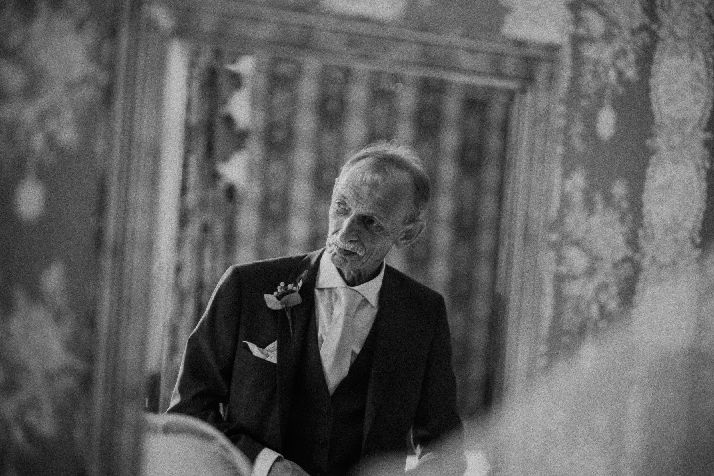 Black and white photo of emotional father of the bride reflected in the mirror