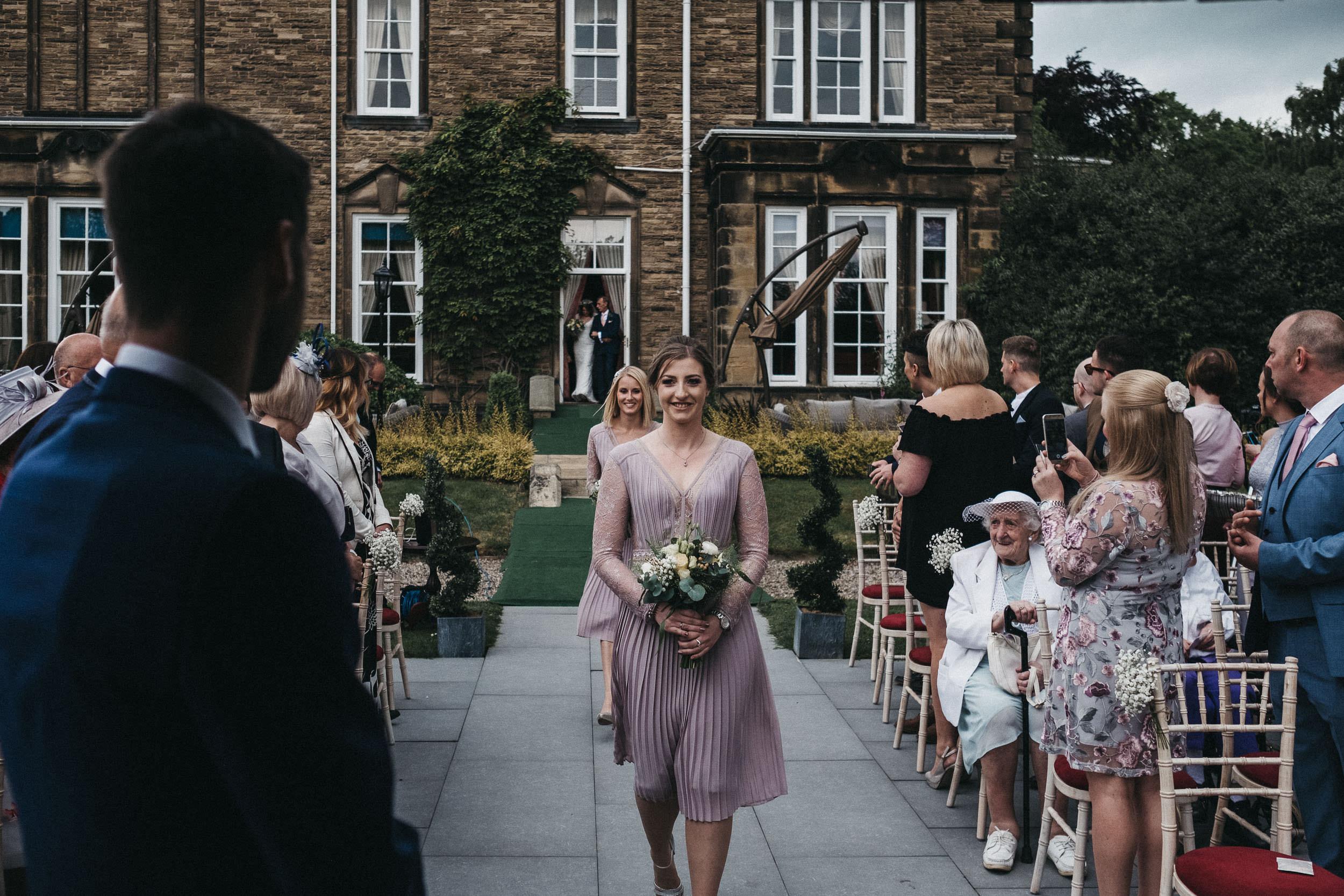 Bridesmaids walk down aisle smiling