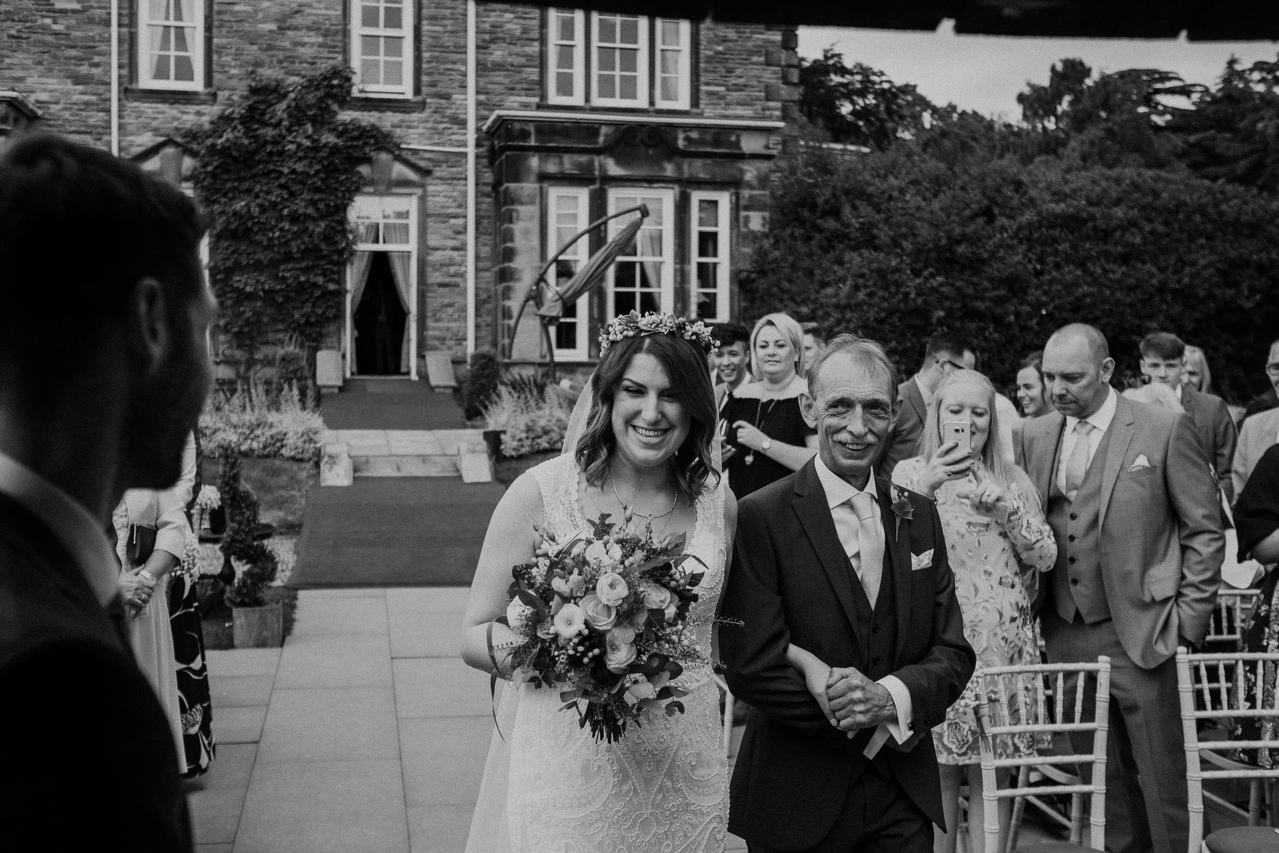 Black and white photo of bride and father of the bride smiling at the groom as they arrive at the wedding ceremony