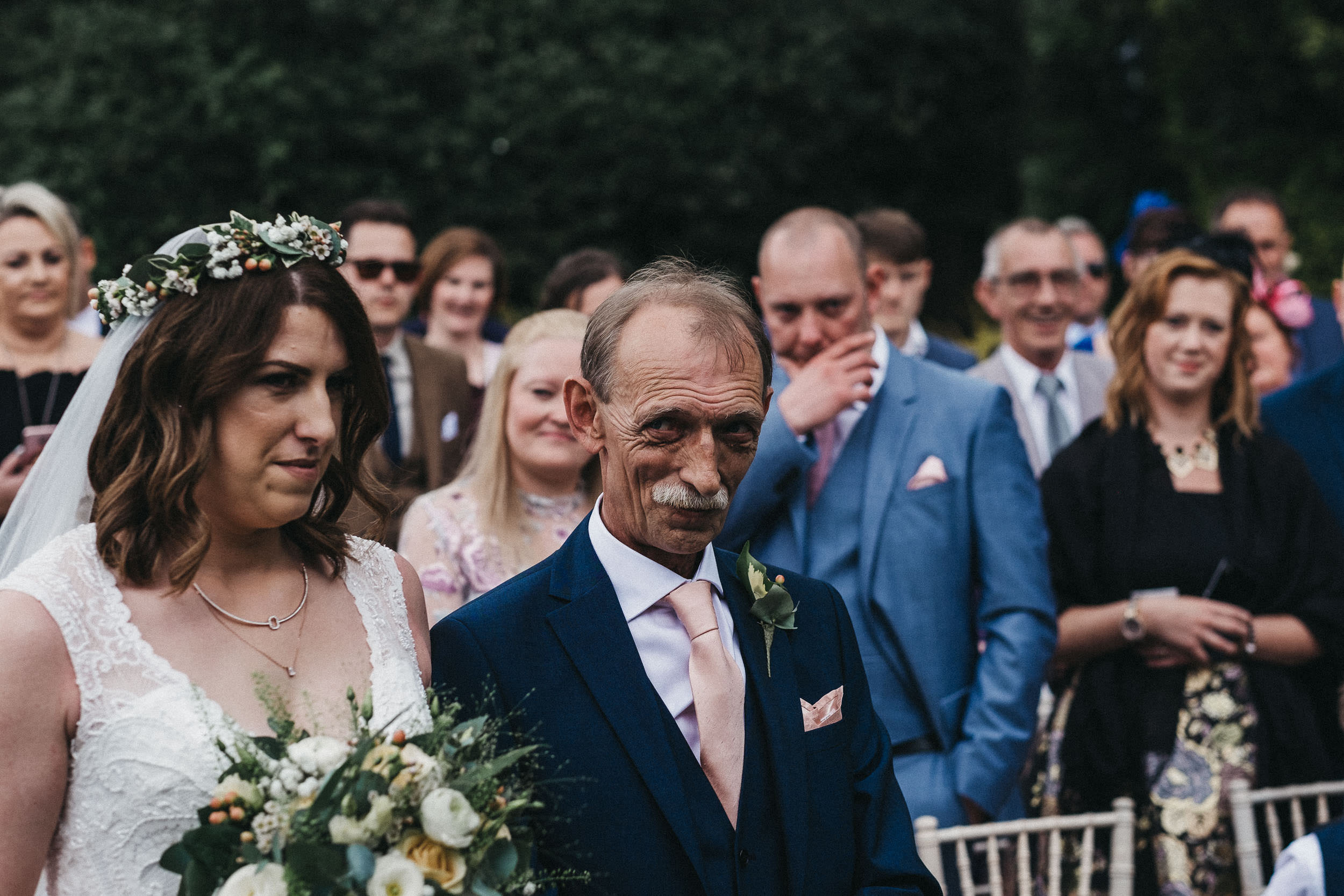 Father of bride gives cheeky smirk to groom