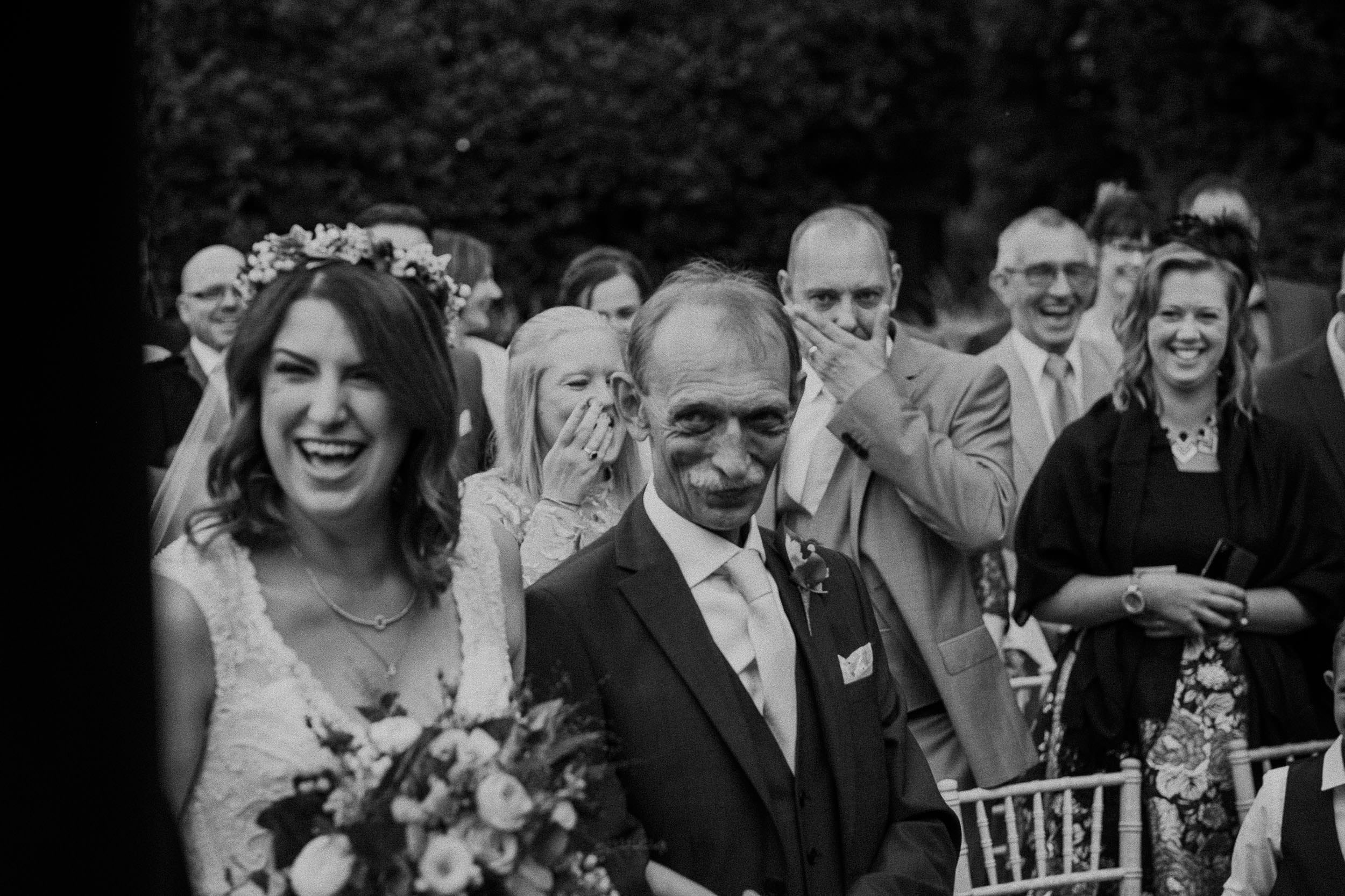 Black and white photo of bride and father of bride laughing while guests look on