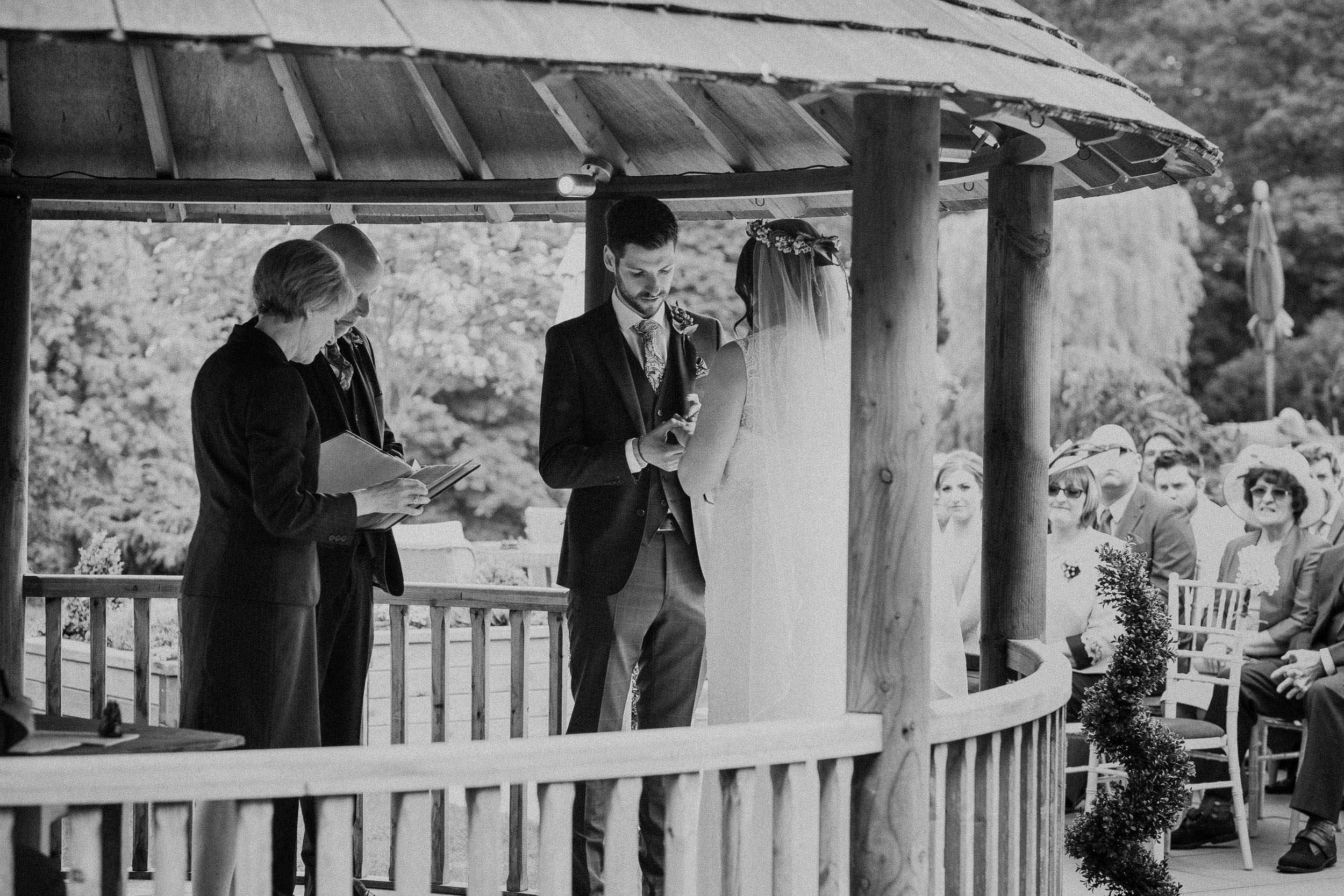 Black and white photo of bride and groom exchanging rings