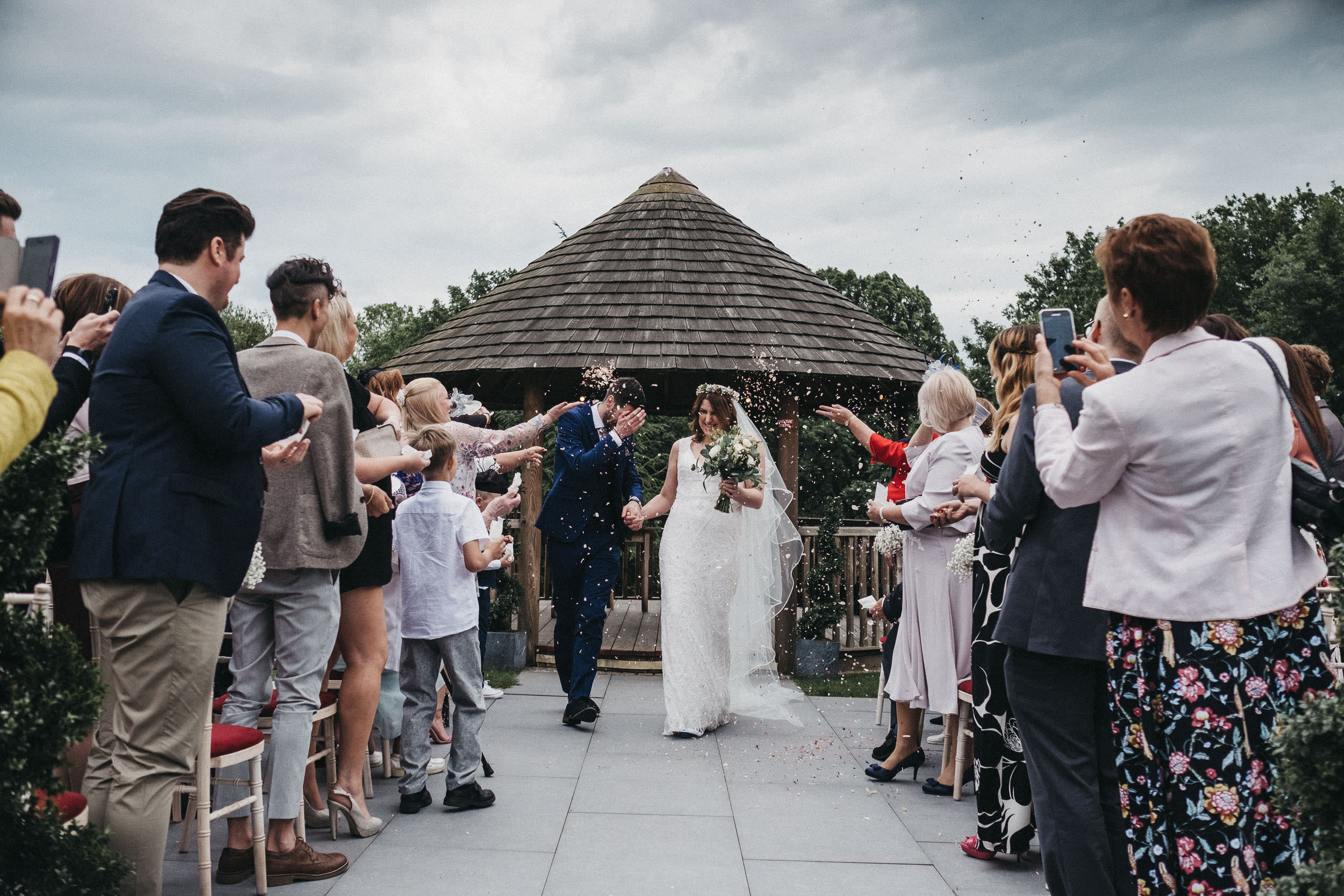 Guests throw confetti in grooms face