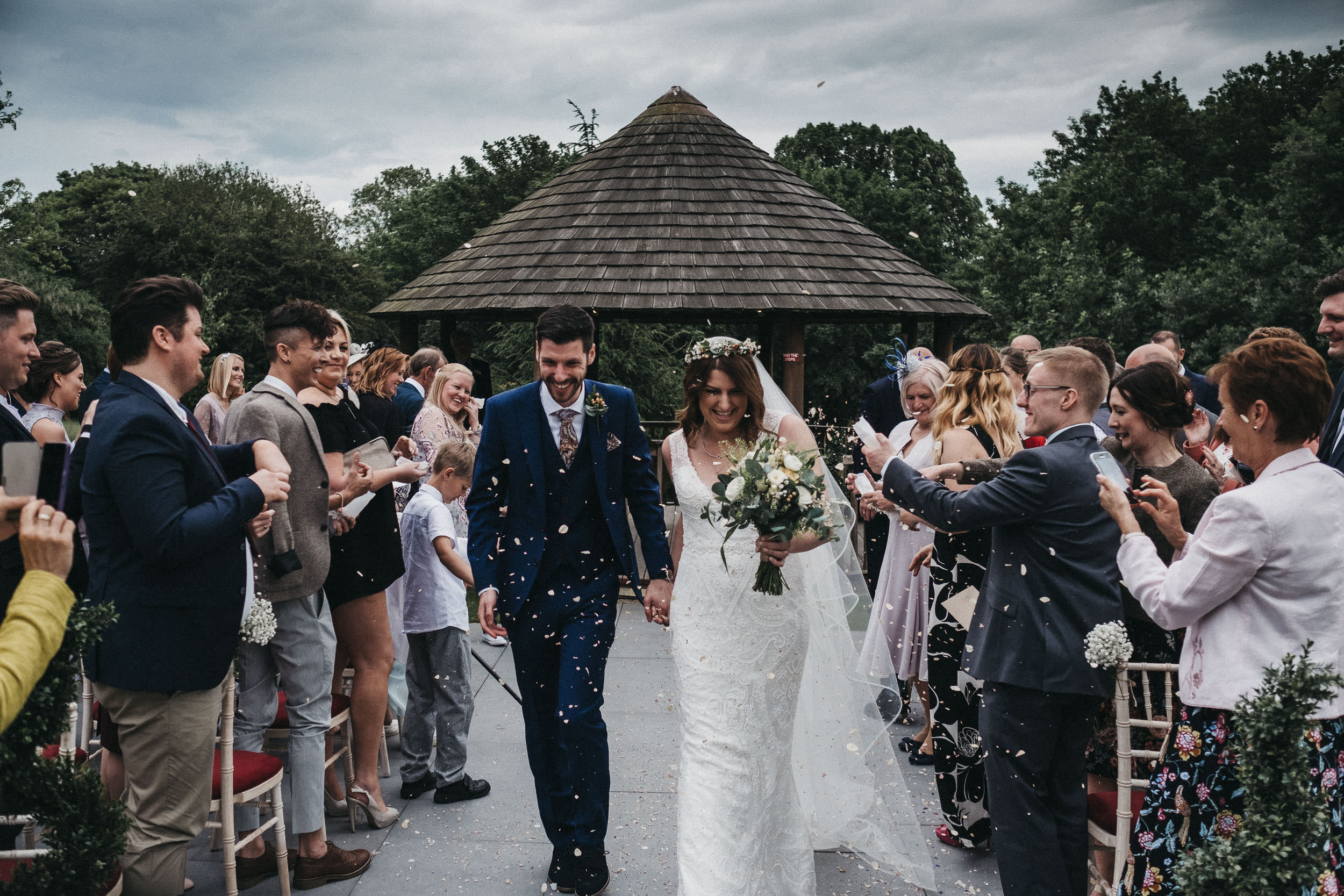 Bride and groom laugh as they are showered in confetti