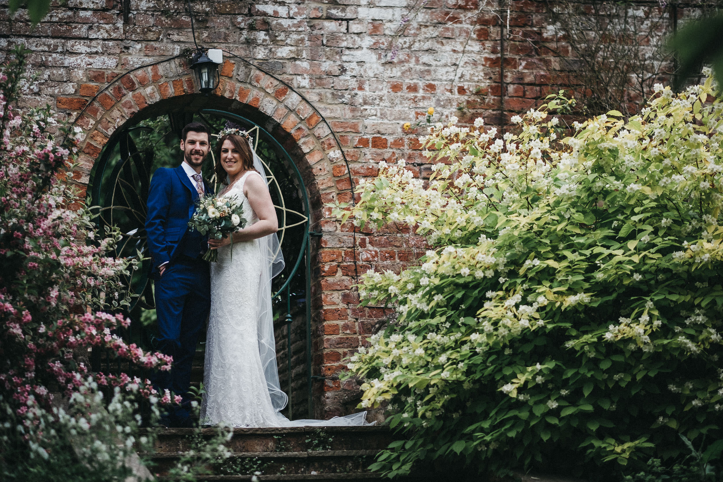 Bride and groom pose on steps surrounded by flowers