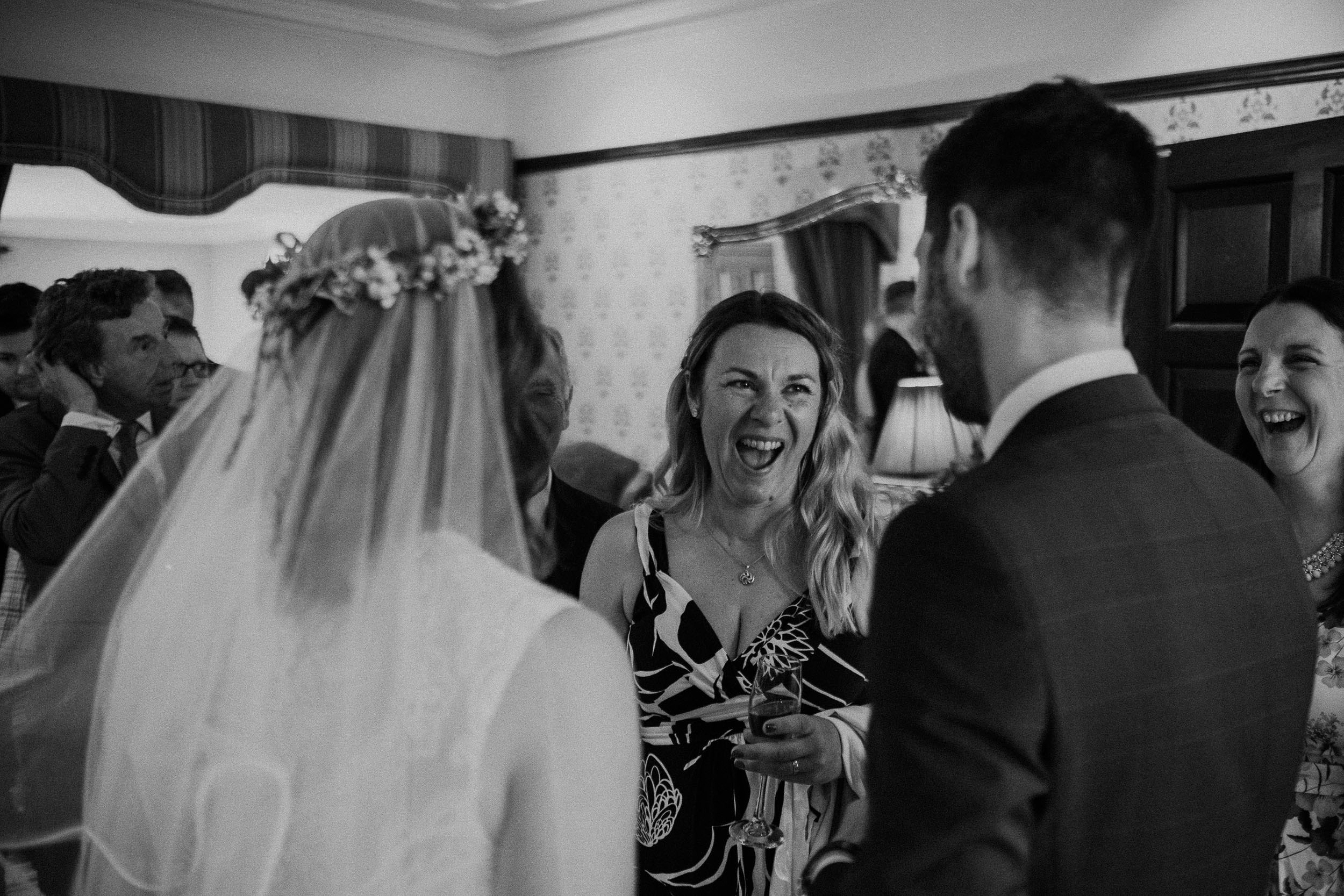 Black and white photo of guest laughing at wedding