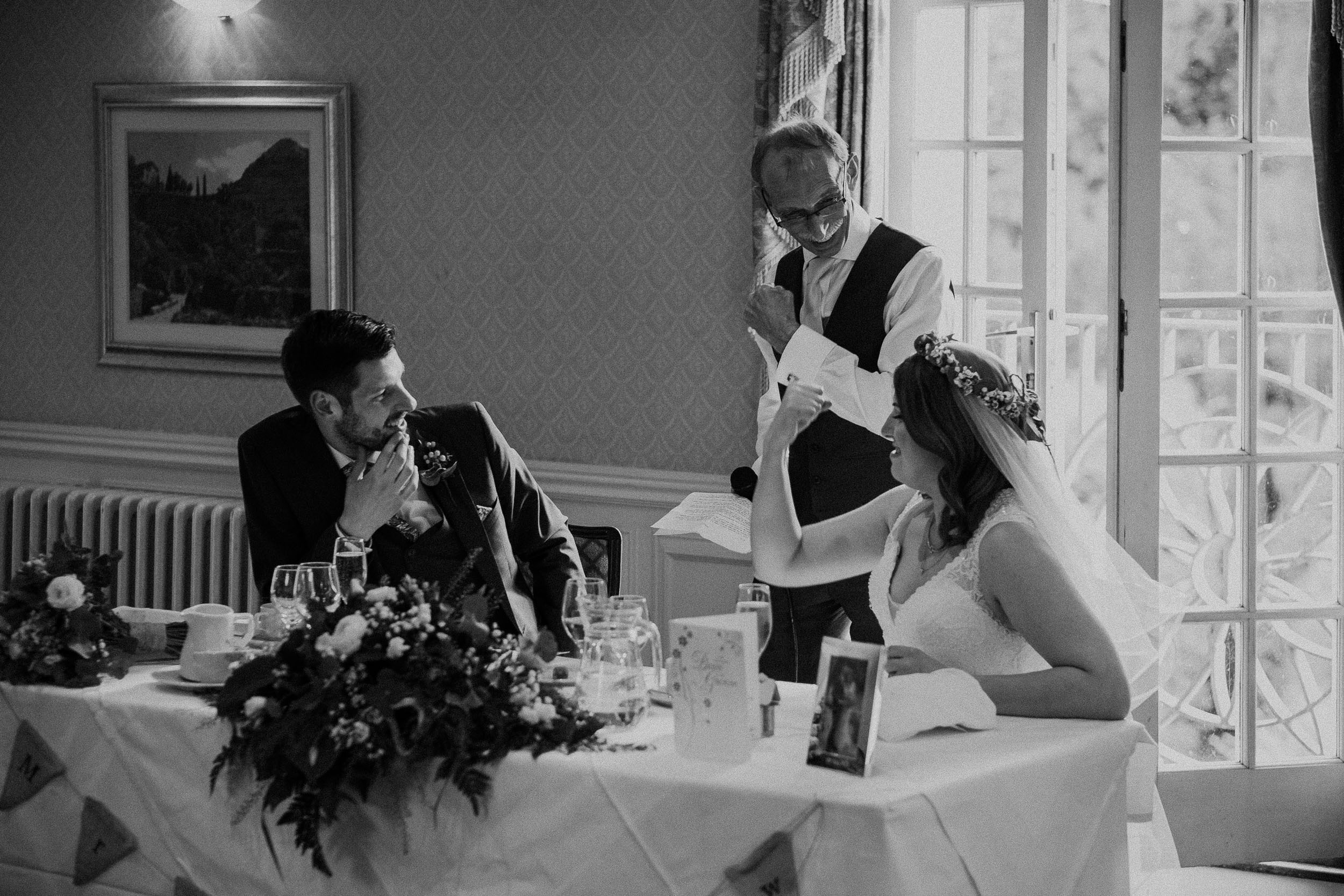 Black and white photo of bride and father of bride flexing muscles
