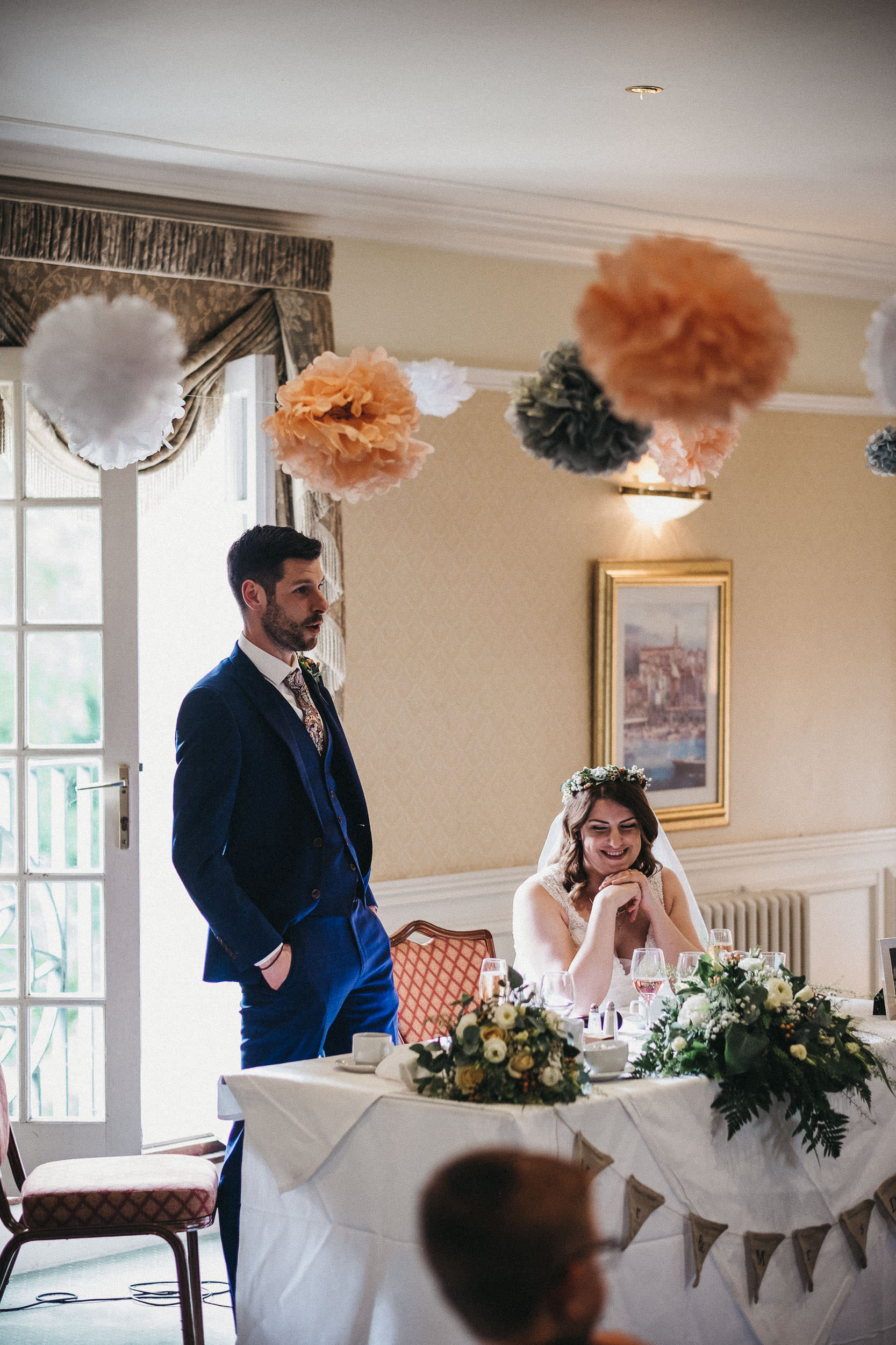Bride smiling while groom gives wedding speech