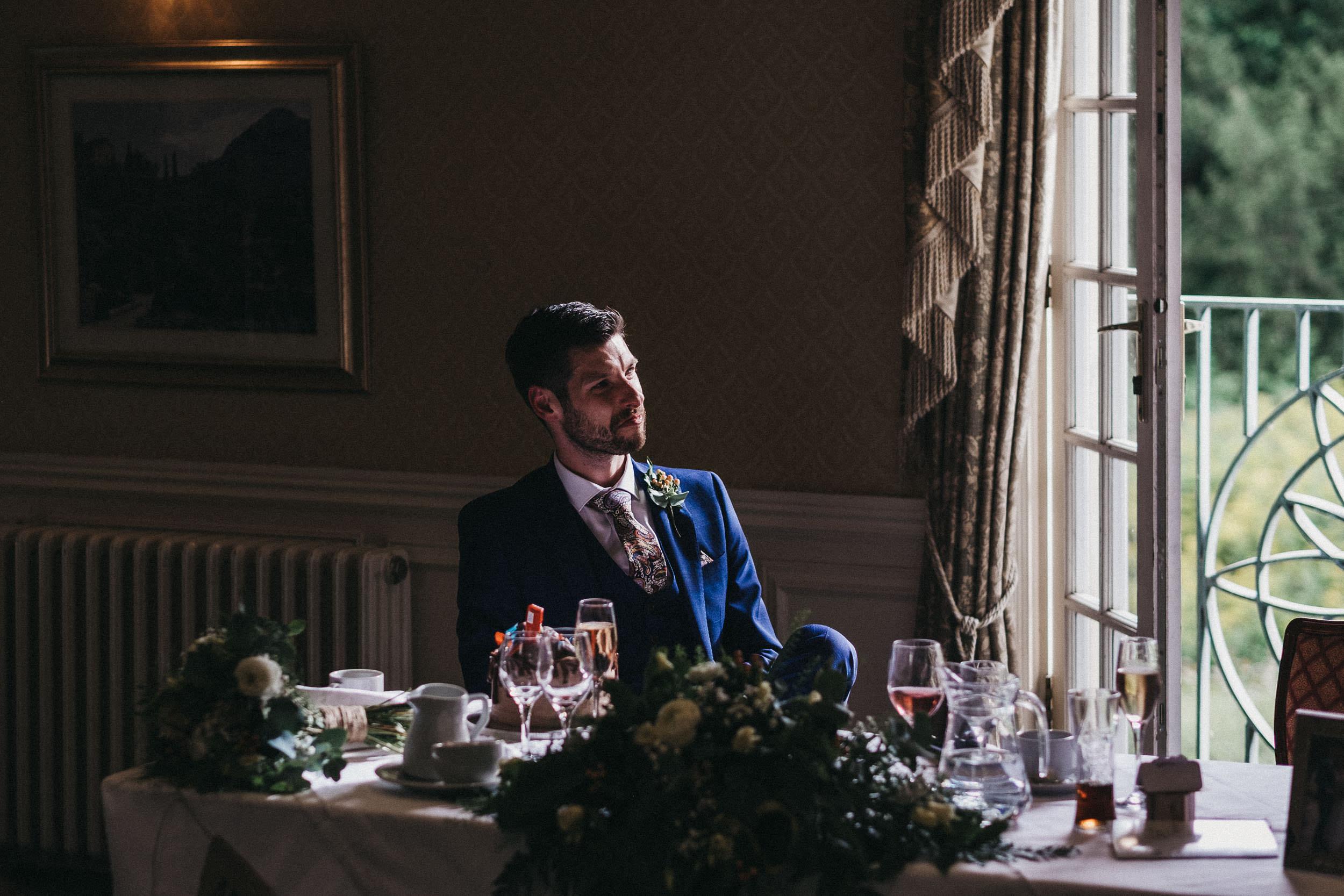Moody photo of groom watching wedding speeches