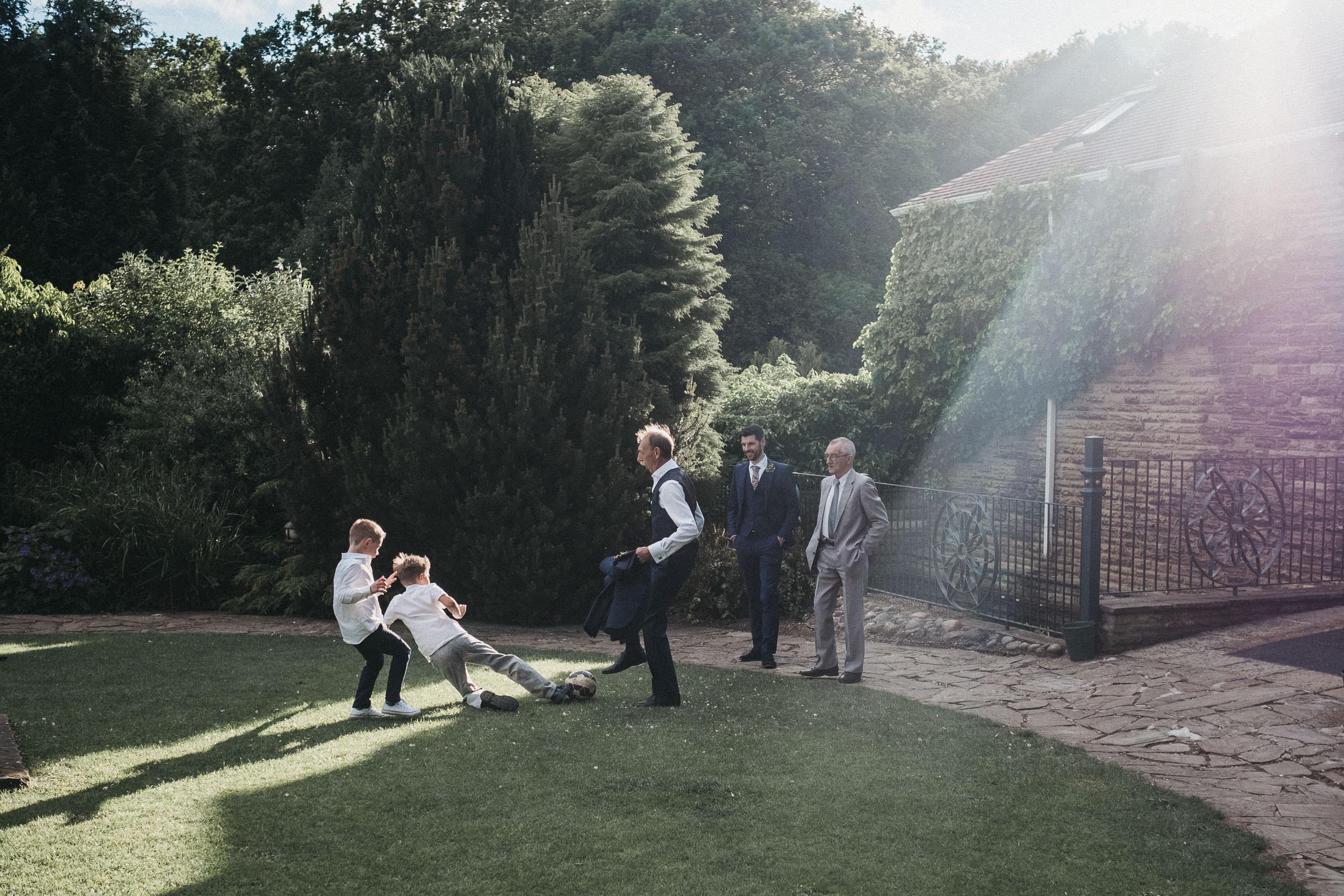 Wedding guests play football in blazing sunlight