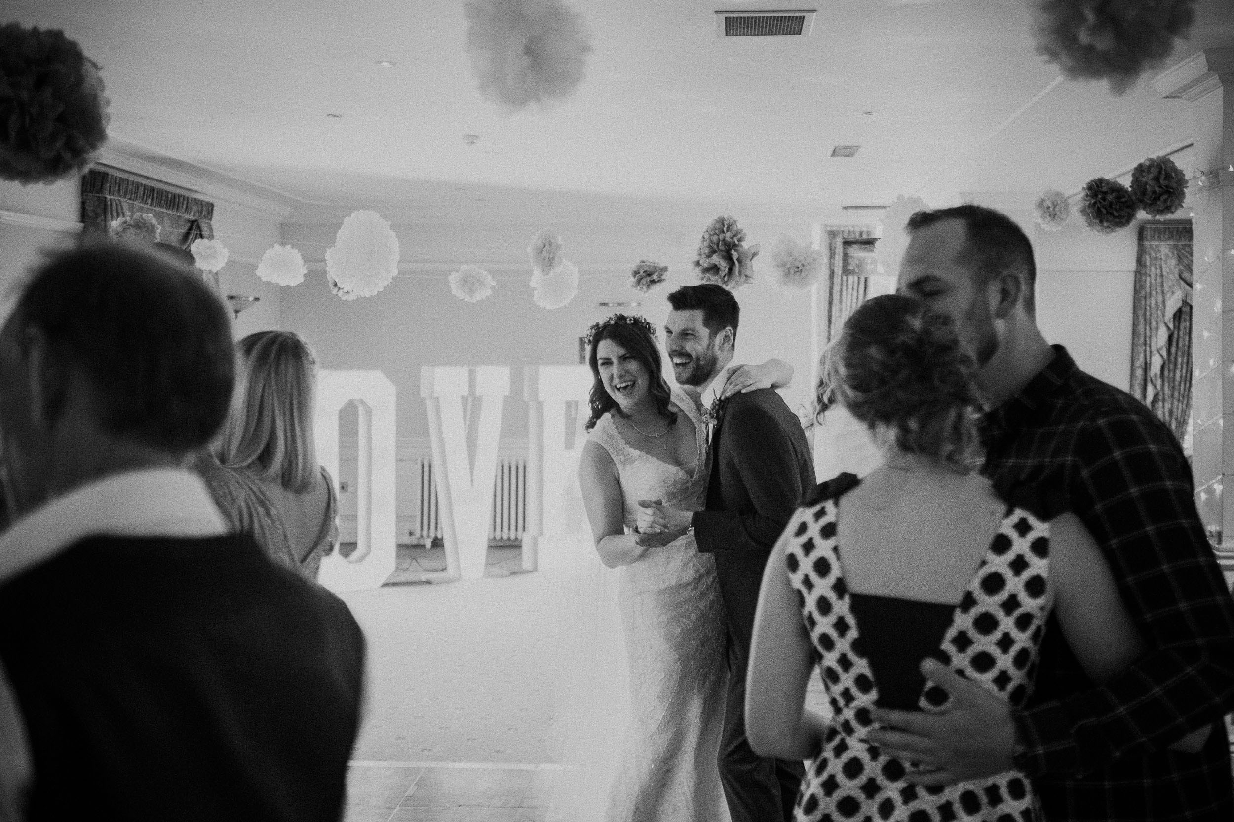 Black and white photo of bride and groom laughing while dancing