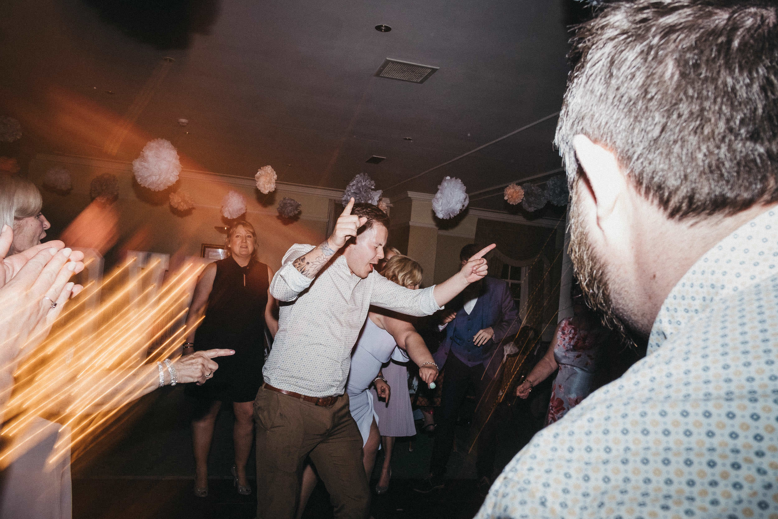 Wedding guest pointing while dancing
