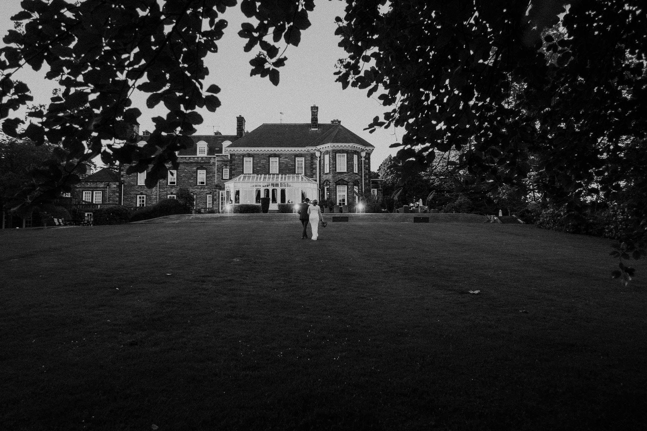 Black and white photo of bride and groom walking up hill toward Judges at Kirklevington