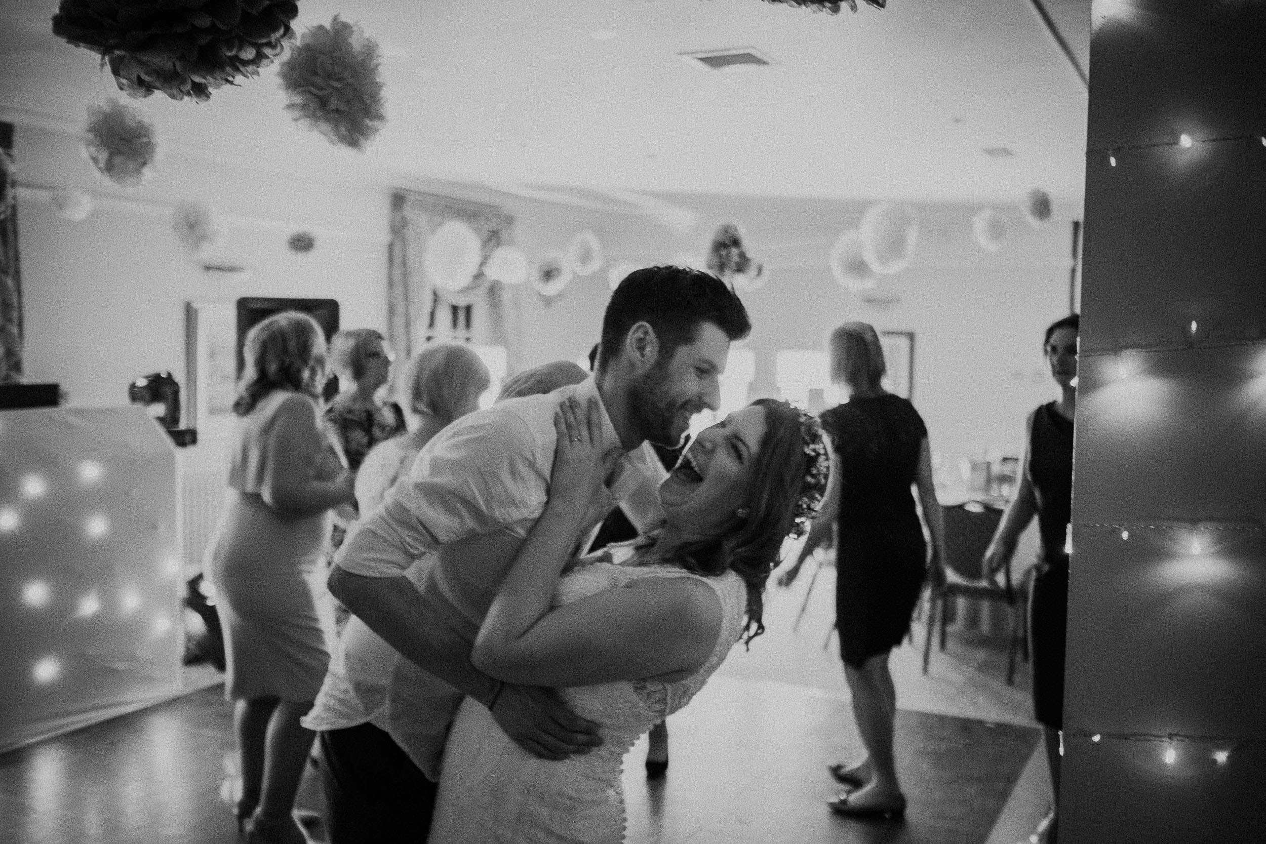 Black and white photo of bride and groom roaring with laughter on dance floor