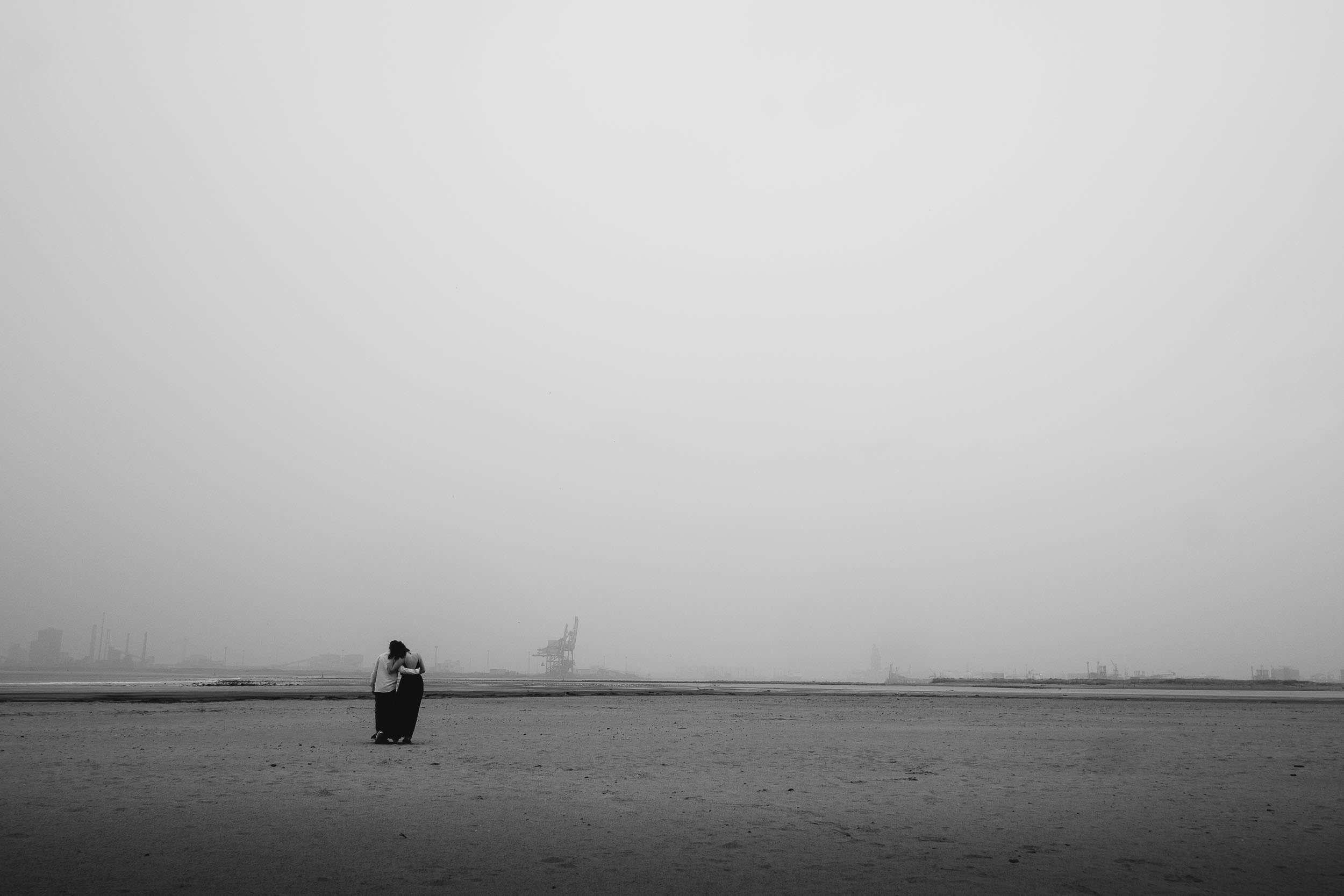 Black and white photo of couple walking on deserted beach arm in arm