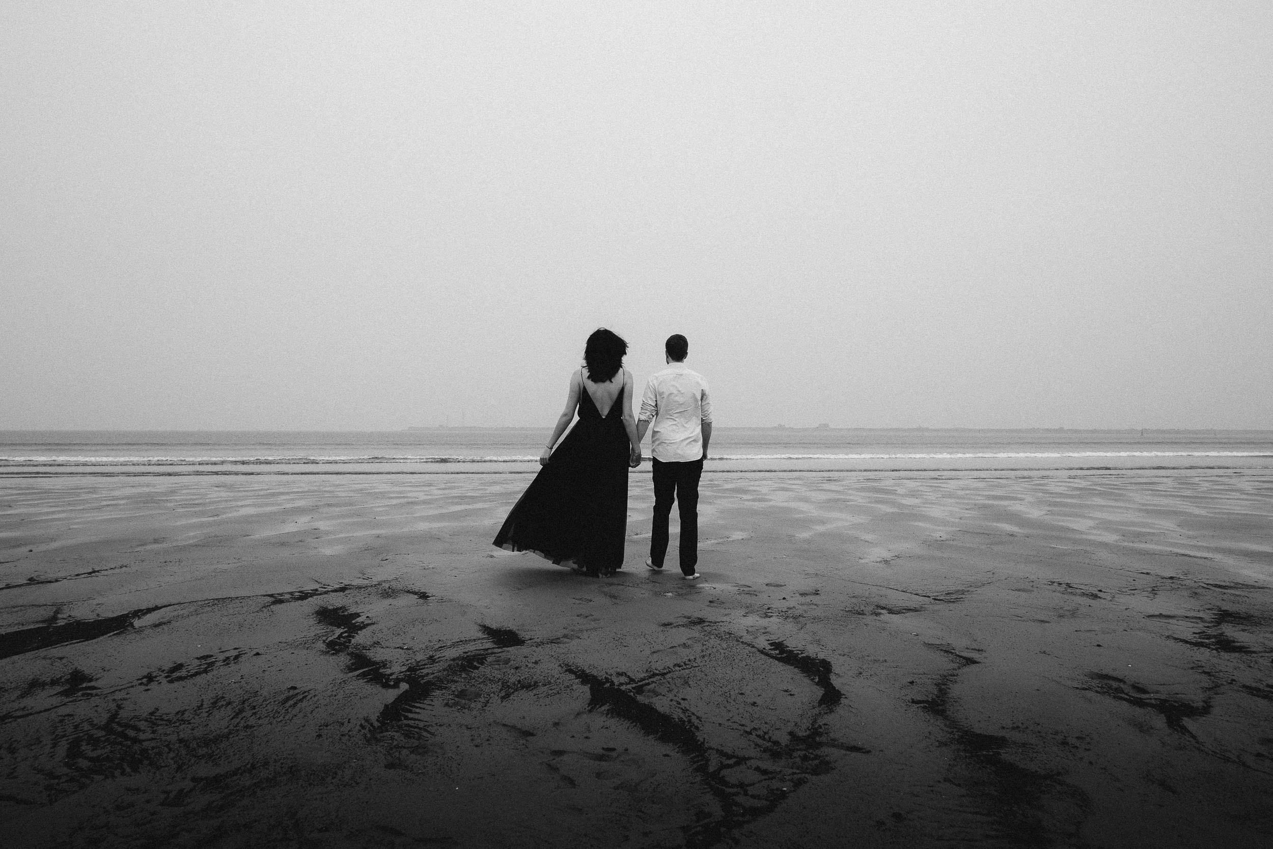 Black and white photo of couple walking toward the sea barefoot