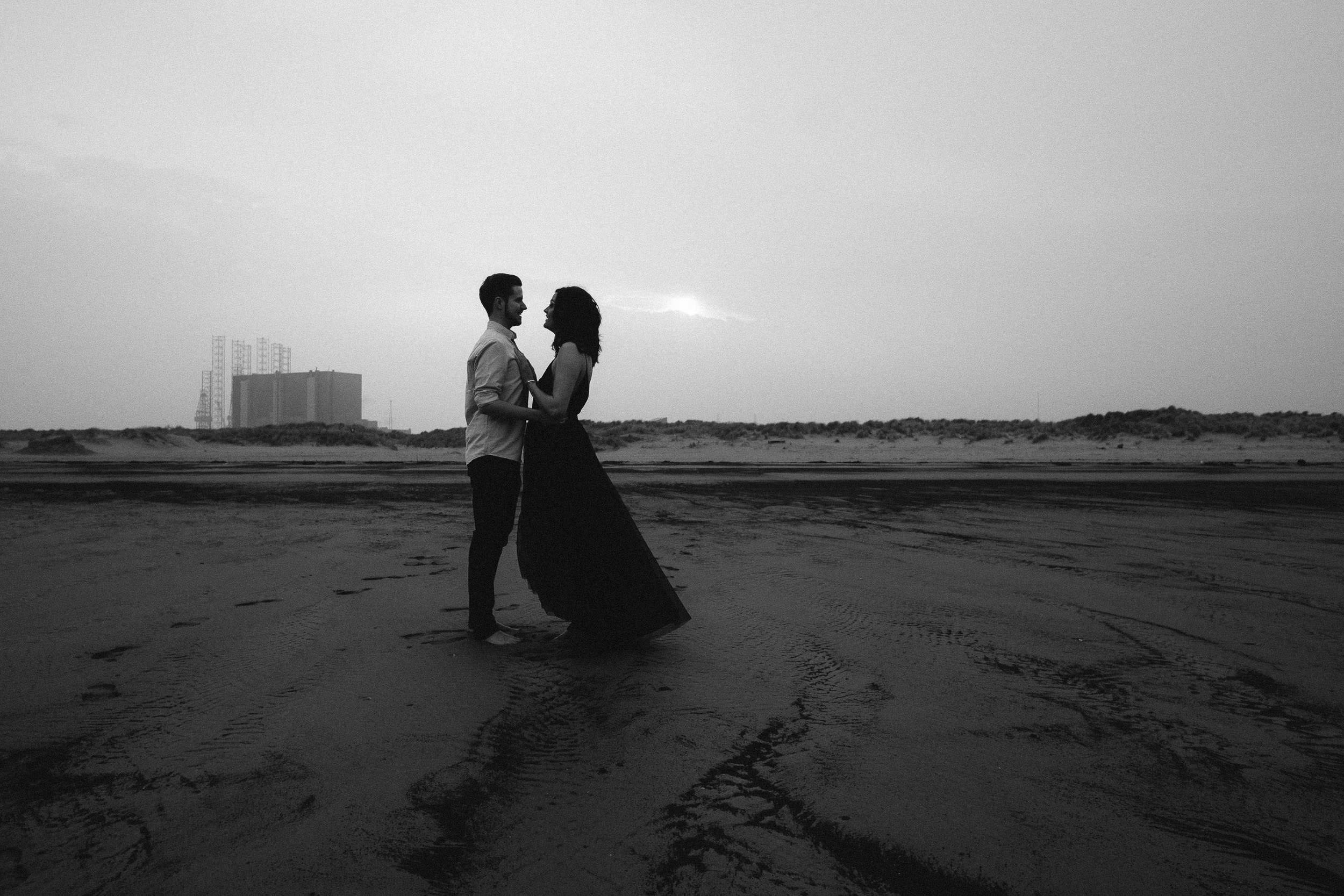 Black and white photo of couple embracing on beach with factory in the background