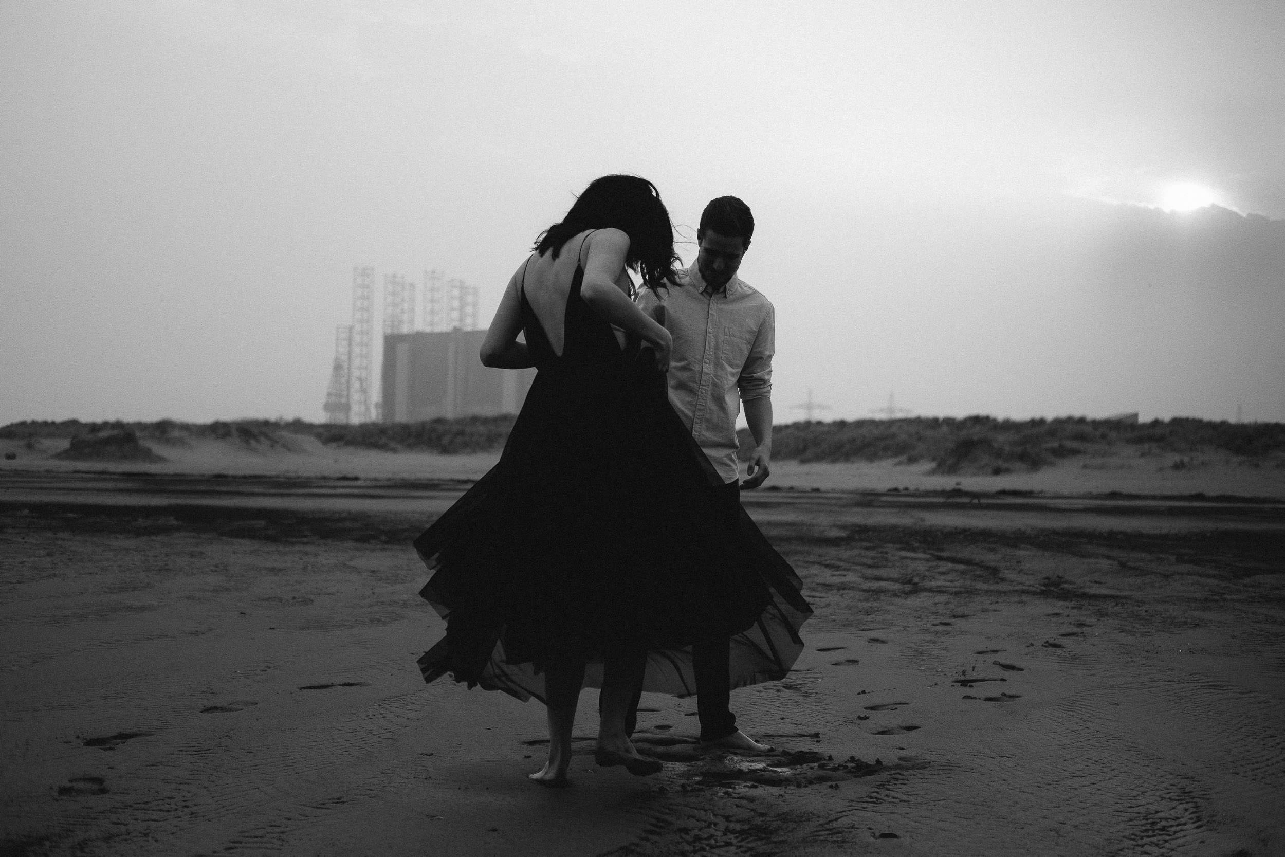 Black and white photo of couple on beach with steelworks behind