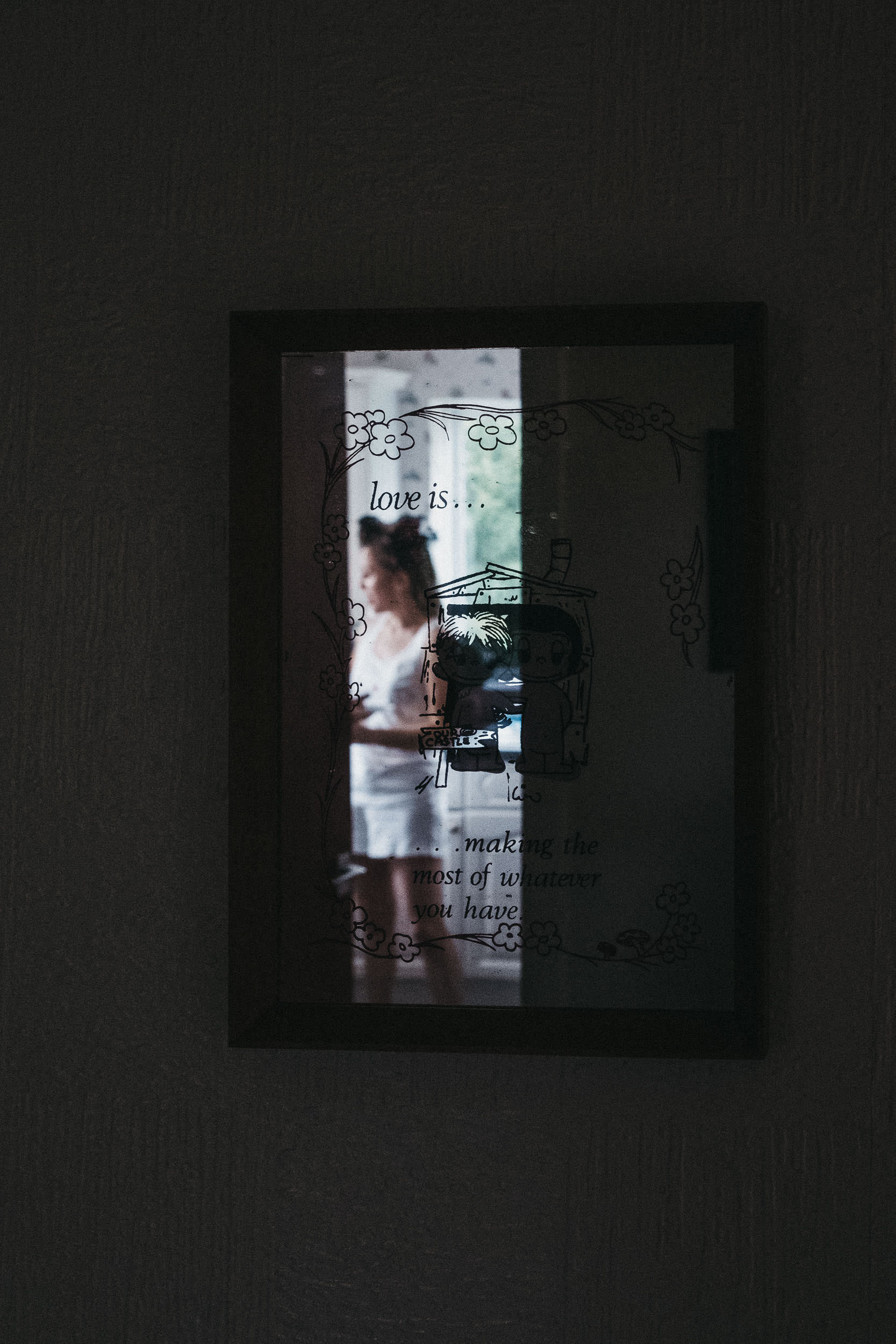 Bride reflected in mirror with Love is quote