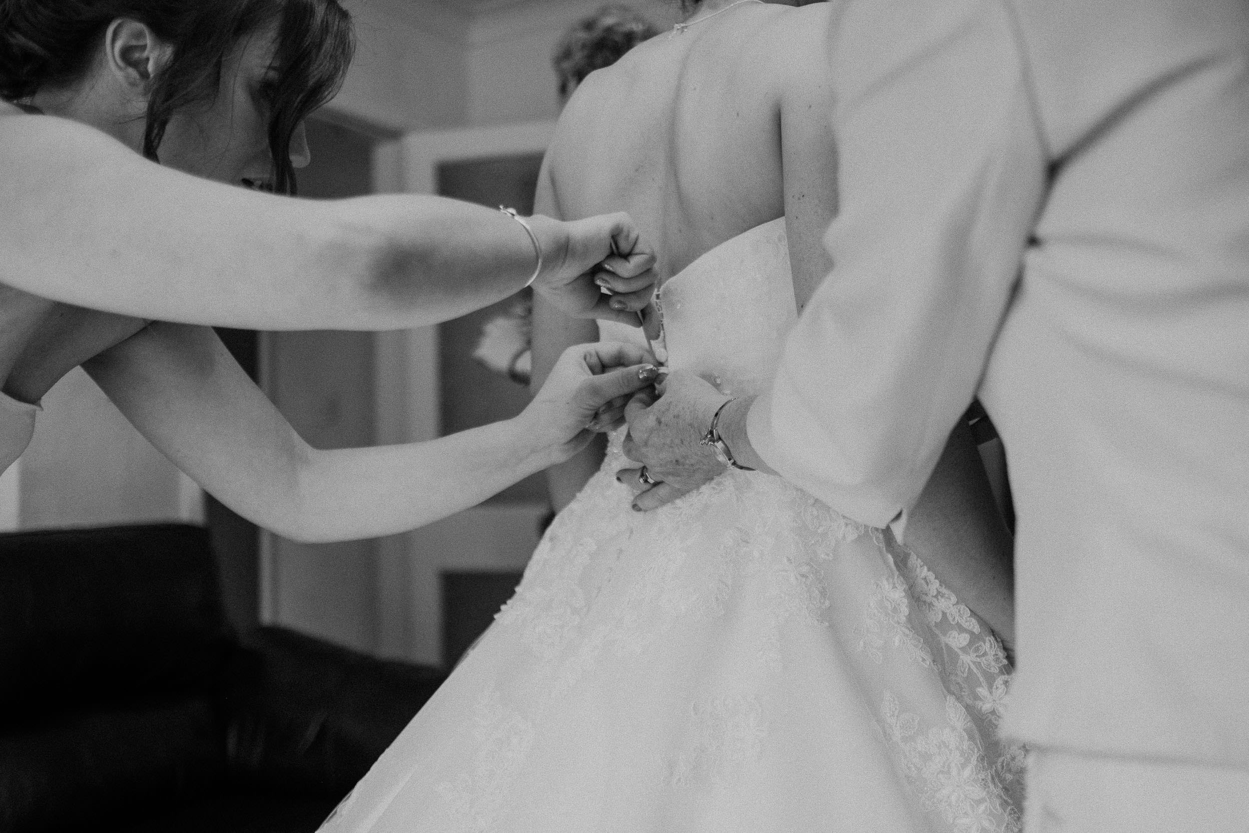 Black and white photo of bridesmaid and mother of the bride fastening wedding dress