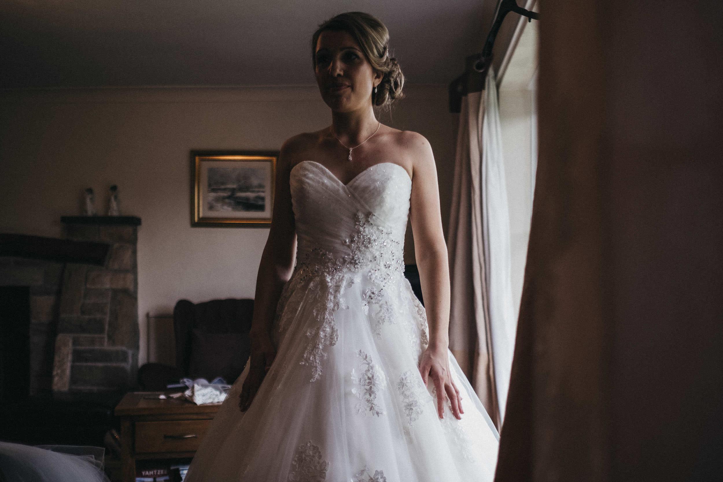 Bride standing near window showing wedding dress details
