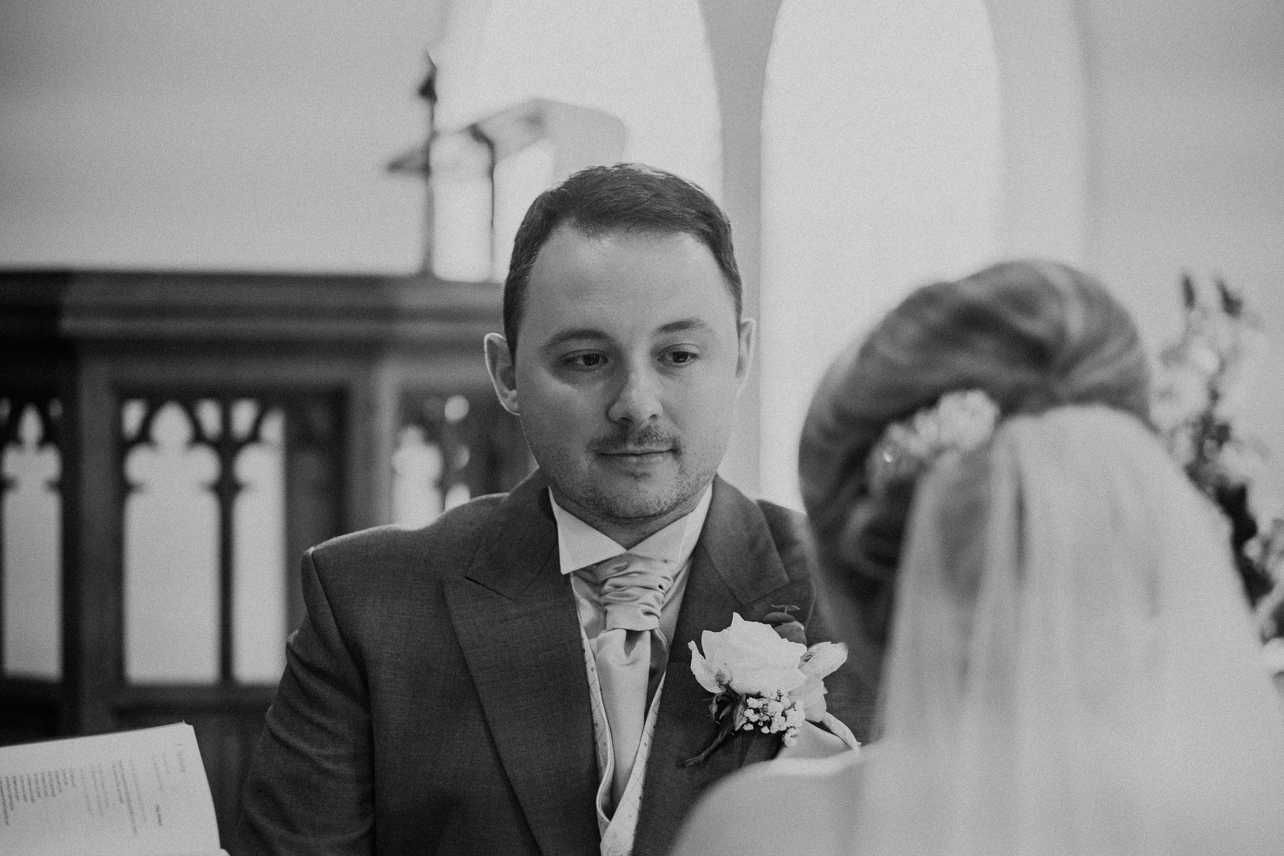 Black and white photo of groom looking lovingly at bride during wedding ceremony