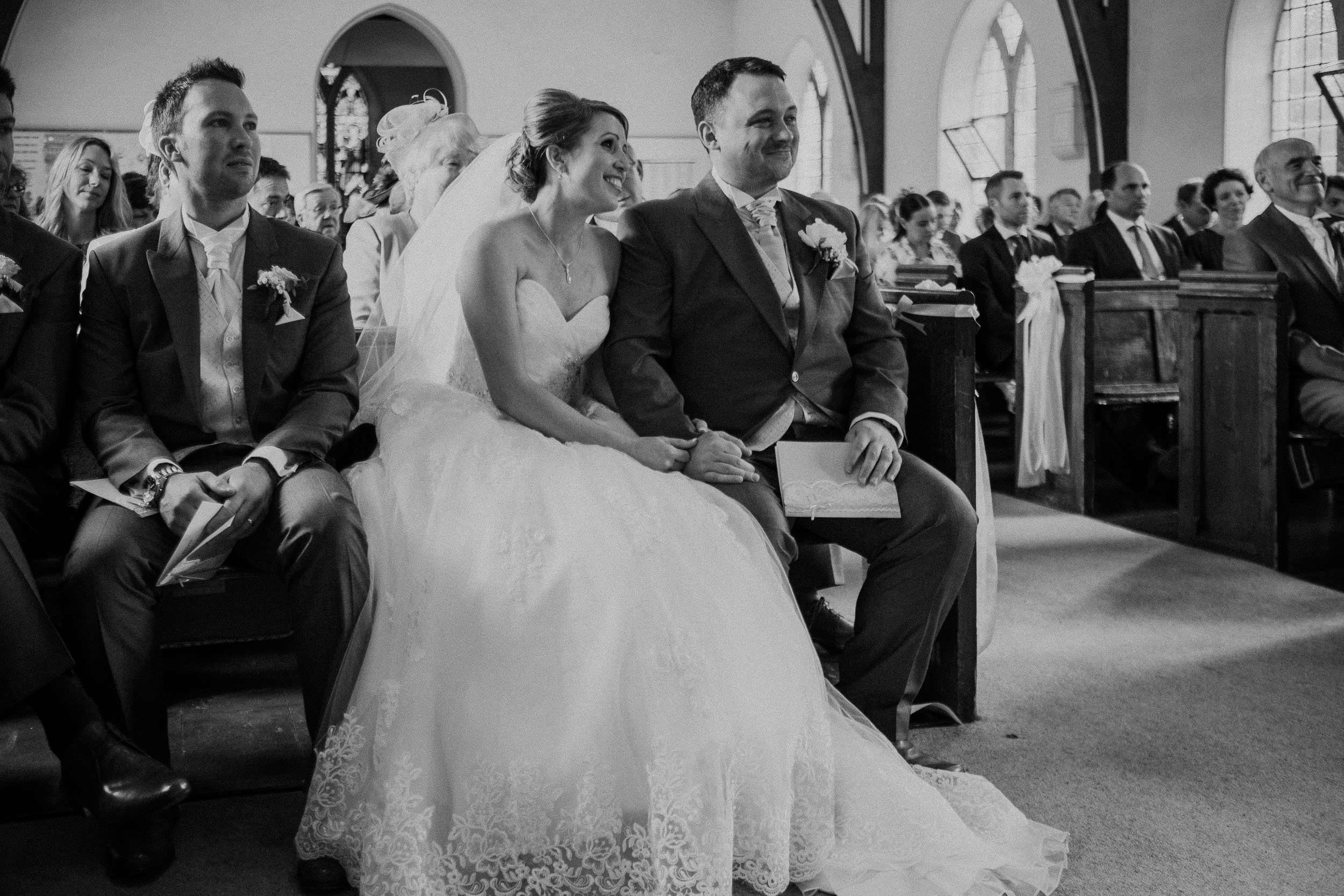 Black and white photo of bride and groom holding hands and smiling during wedding ceremony