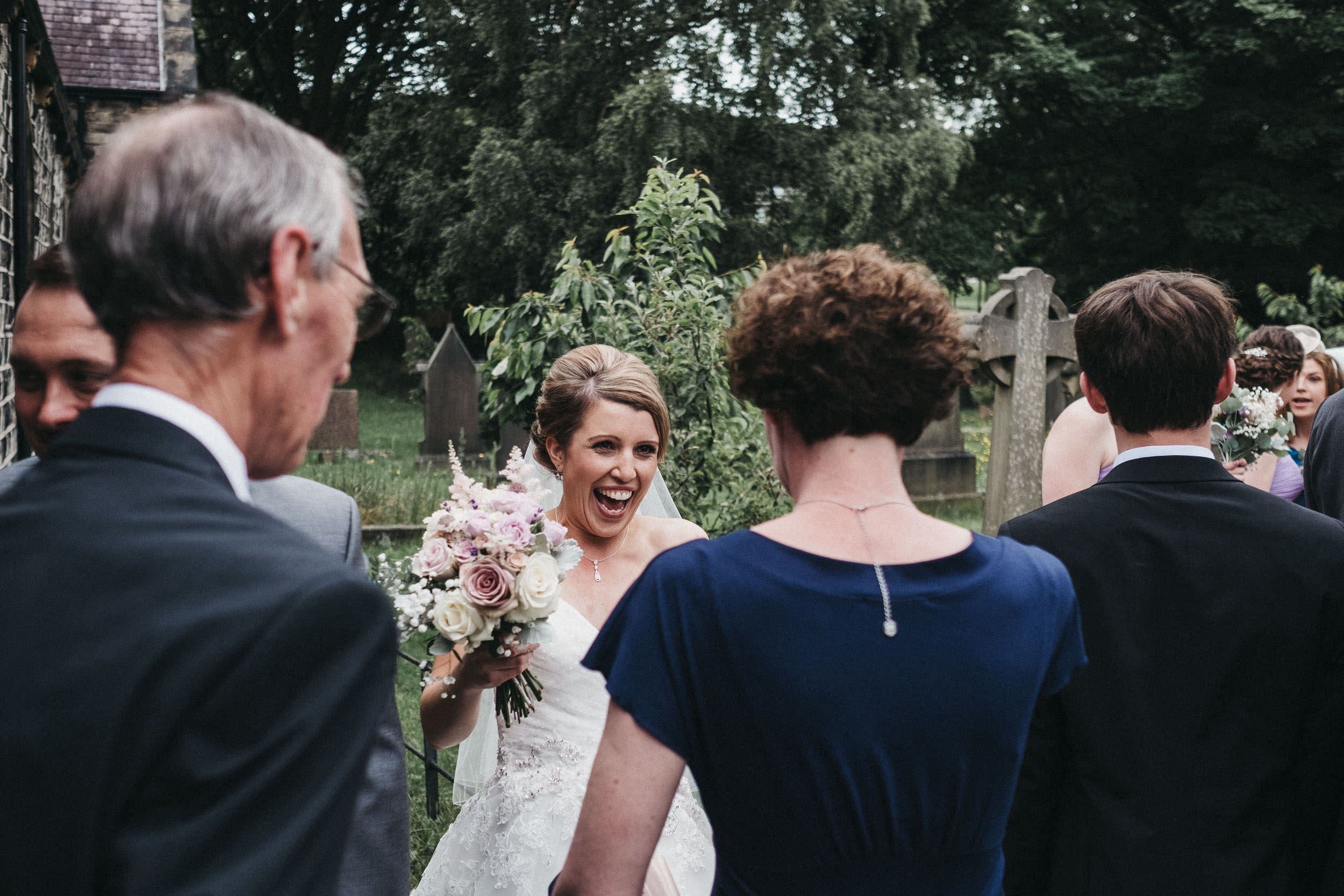 Bride laughing as she greets guests after ceremony
