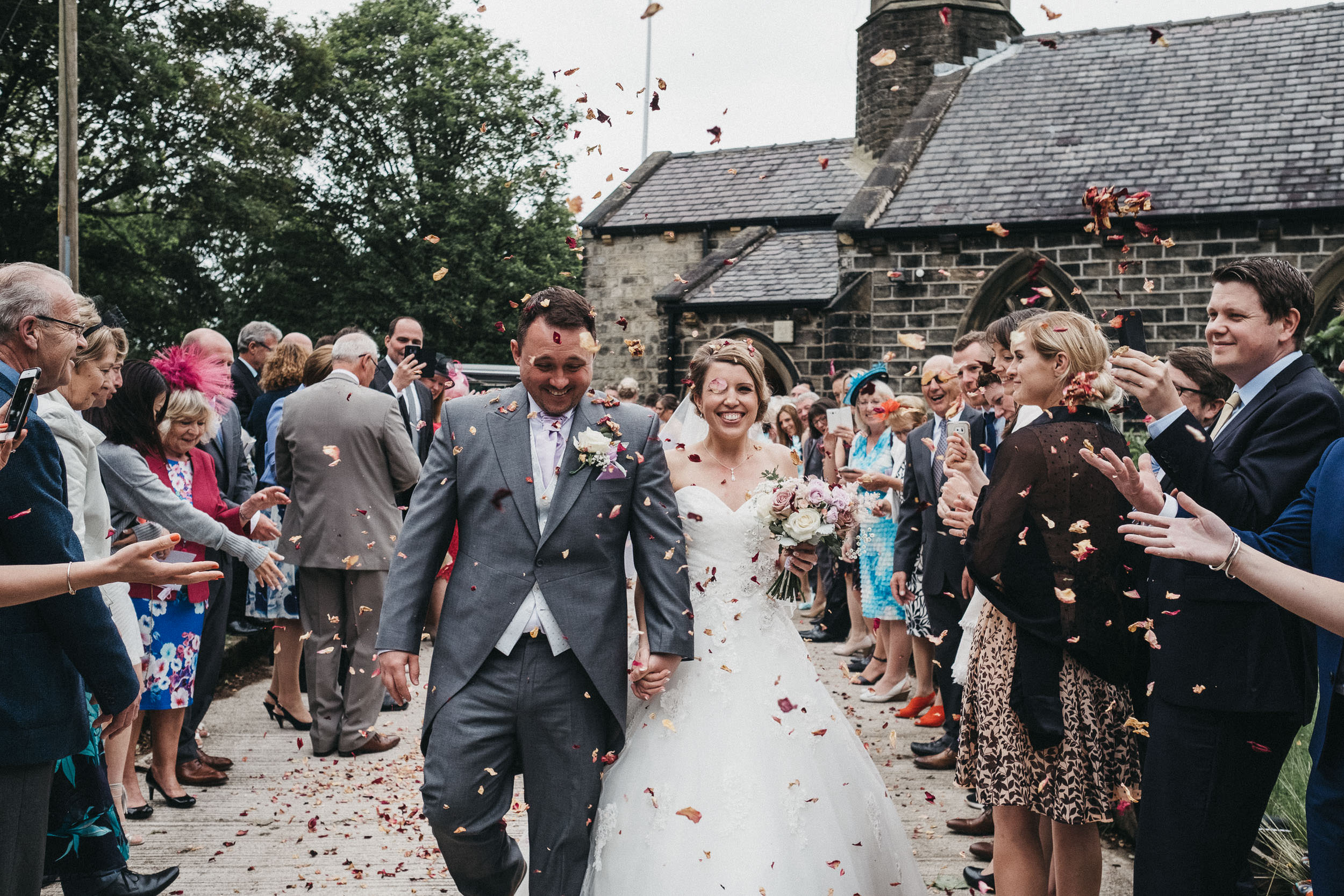 Bride and groom laughing as they are showered with confetti