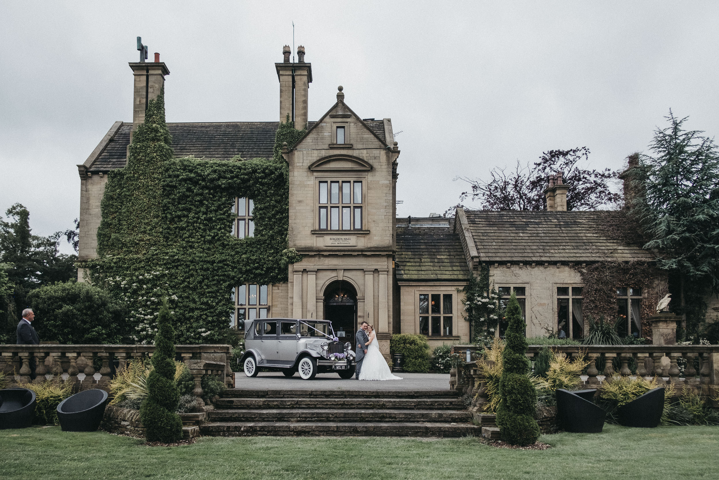 Bride and groom pose with their wedding car with Bagden Hall in the background