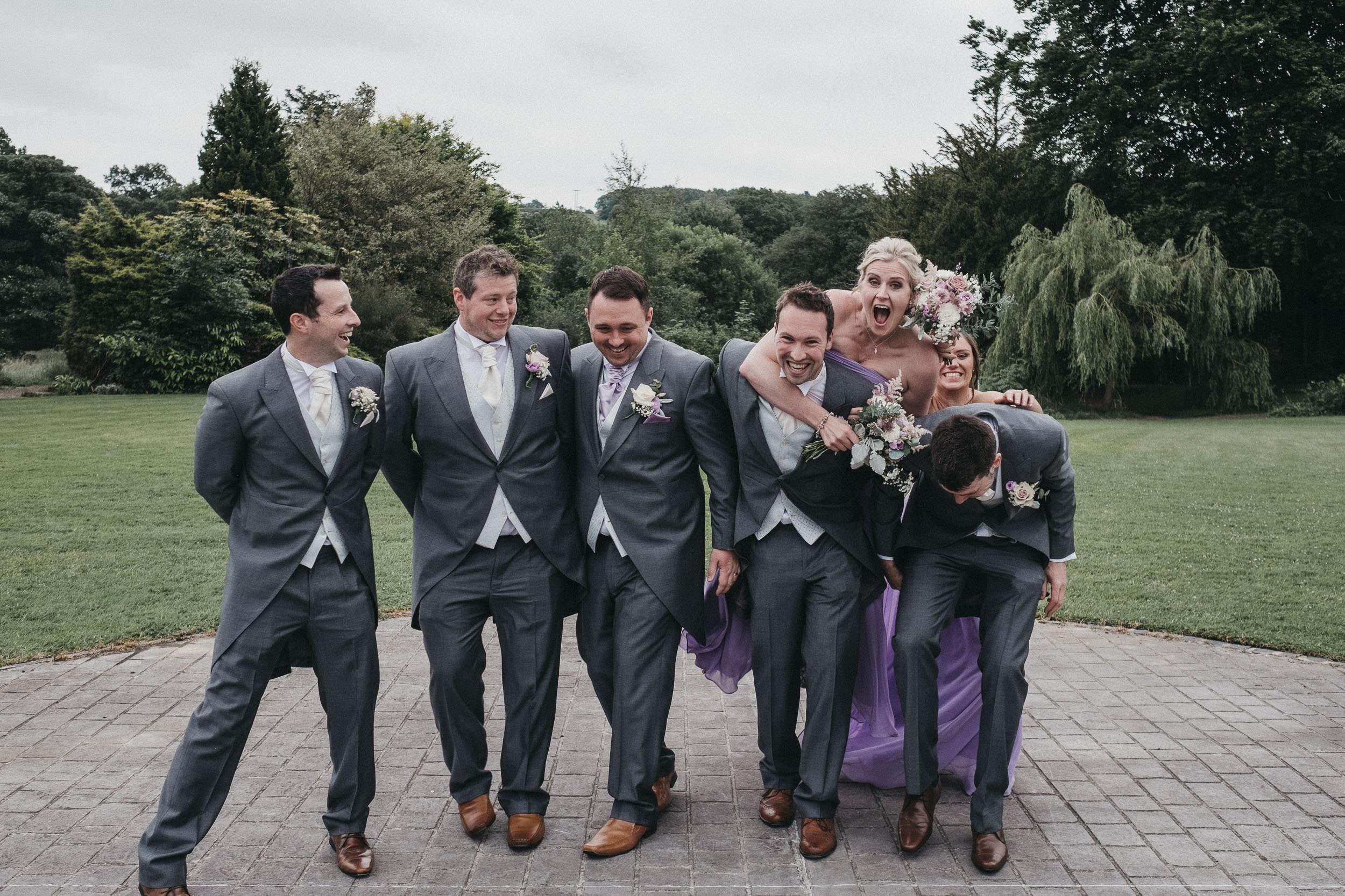 Bridesmaids photobomb the groomsmen group photo