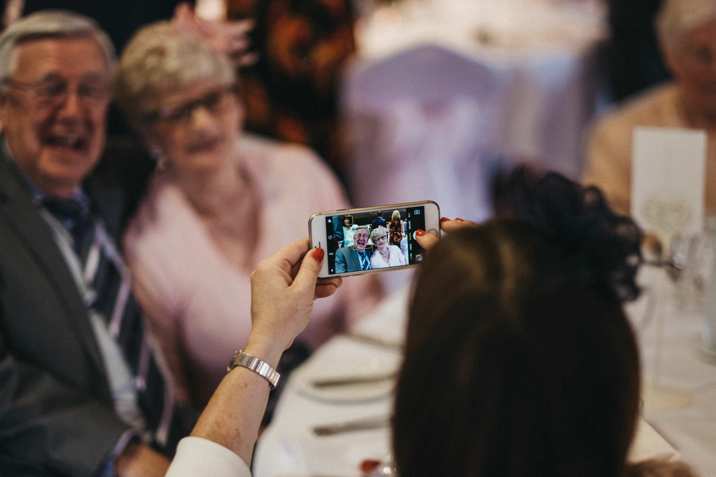 Photo of the back of phone taking a photo os wedding guests