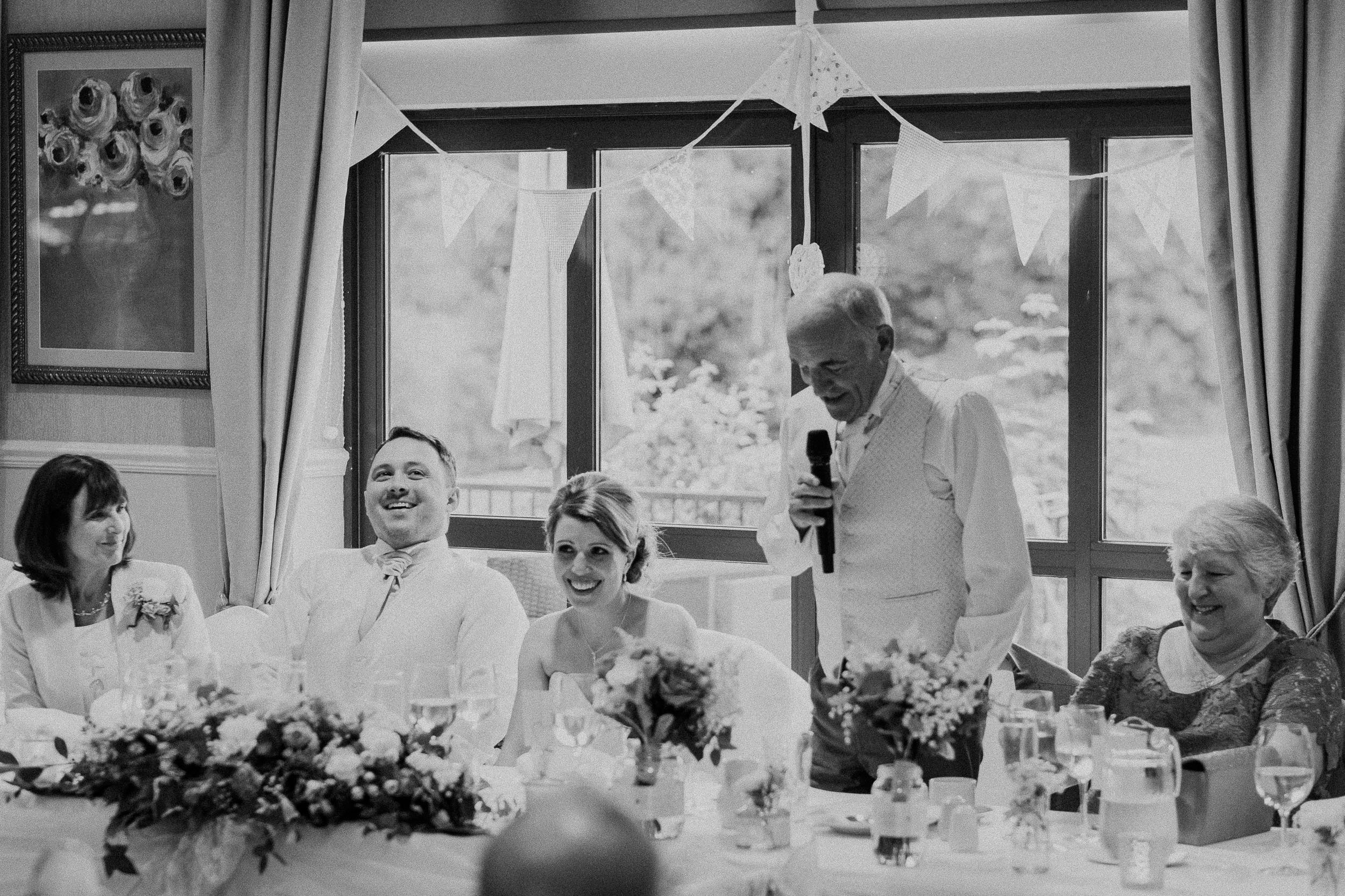 Black and white photo of the father of the bride giving a funny speech