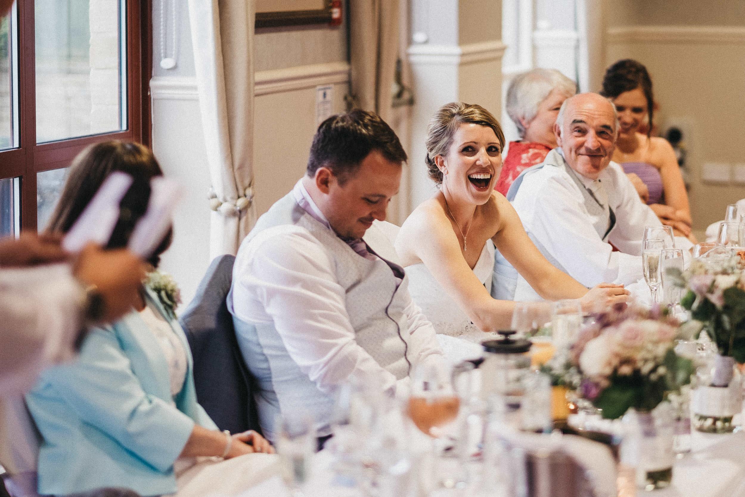 Bride laughing at best man's speech