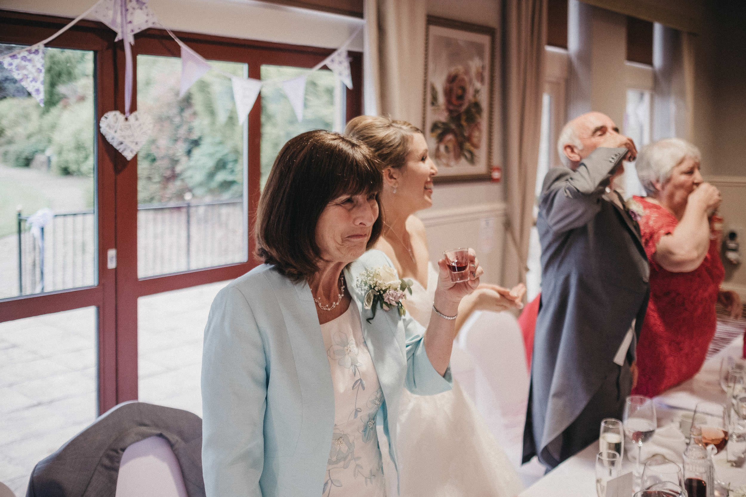 Mother of the groom pulling a funny face after drinking shot